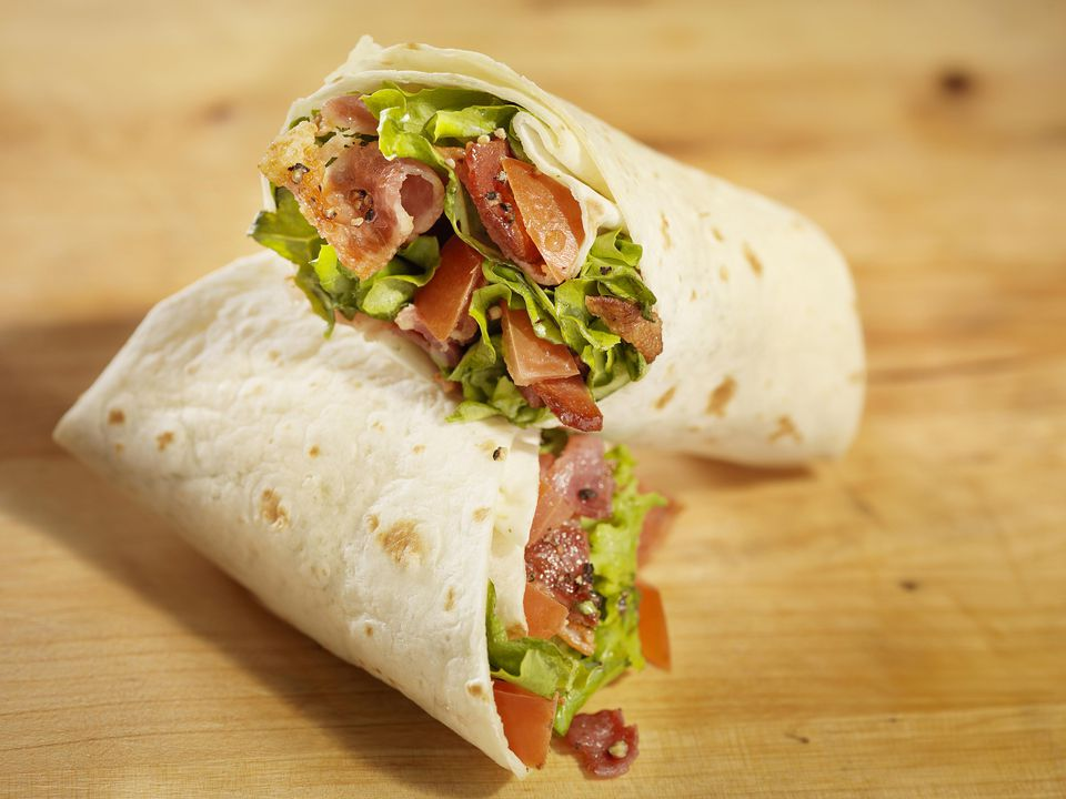 BLT Wrap Sandwich cut in half on a wooden surface