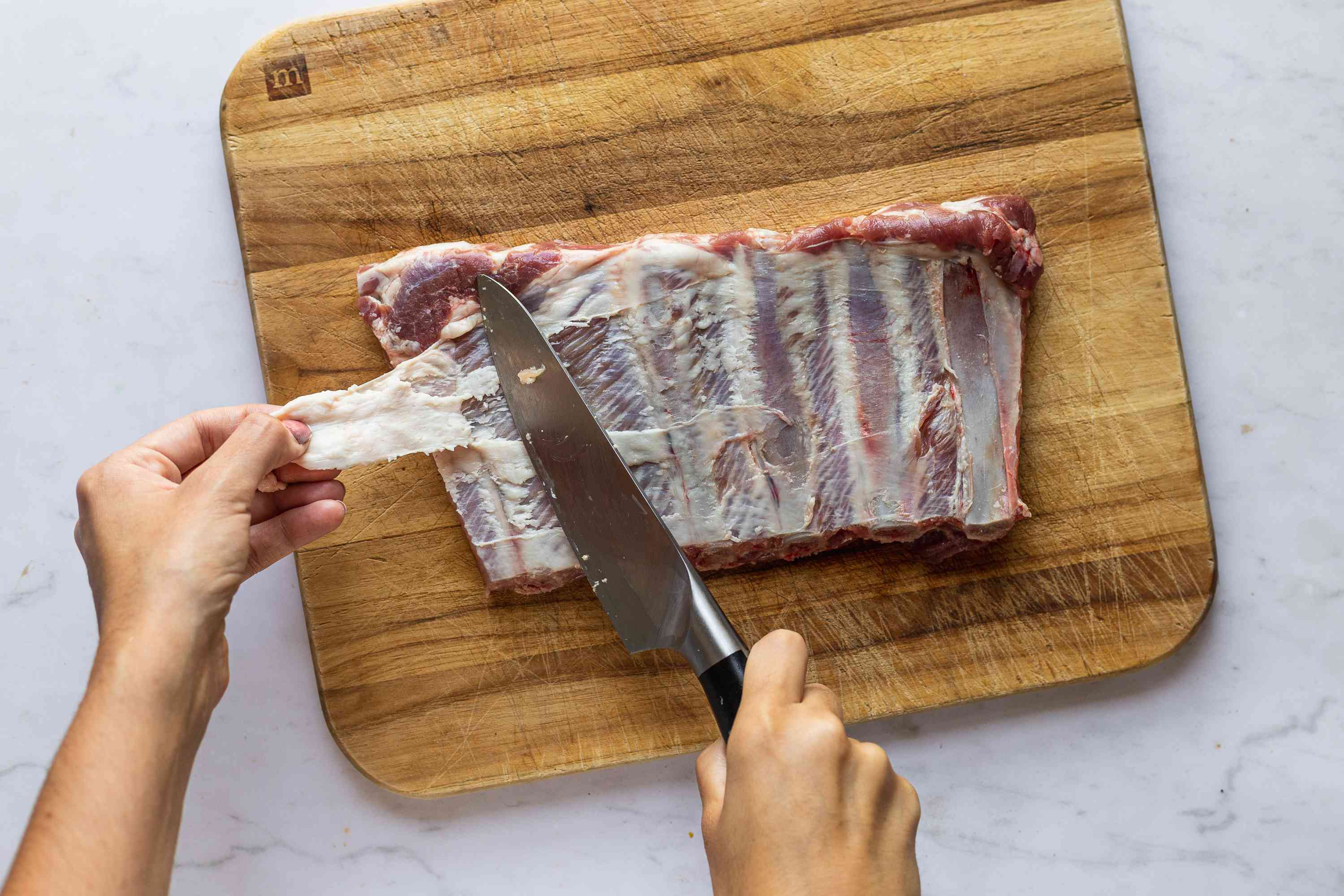 Silverskin from pork ribs being removed on a cutting board