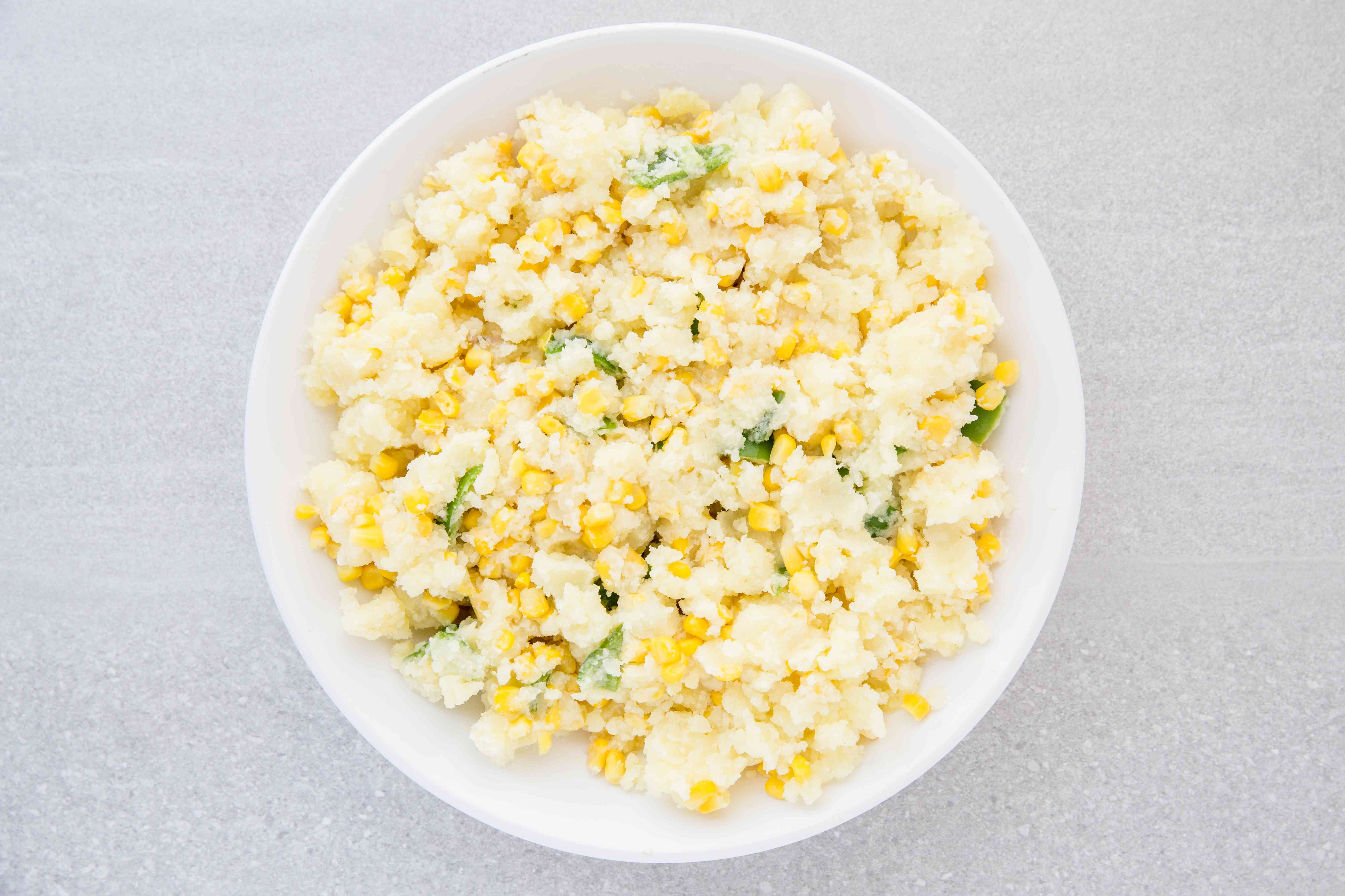Combine corn kernels, potatoes, flour, melted butter, and chopped green bell pepper in a bowl