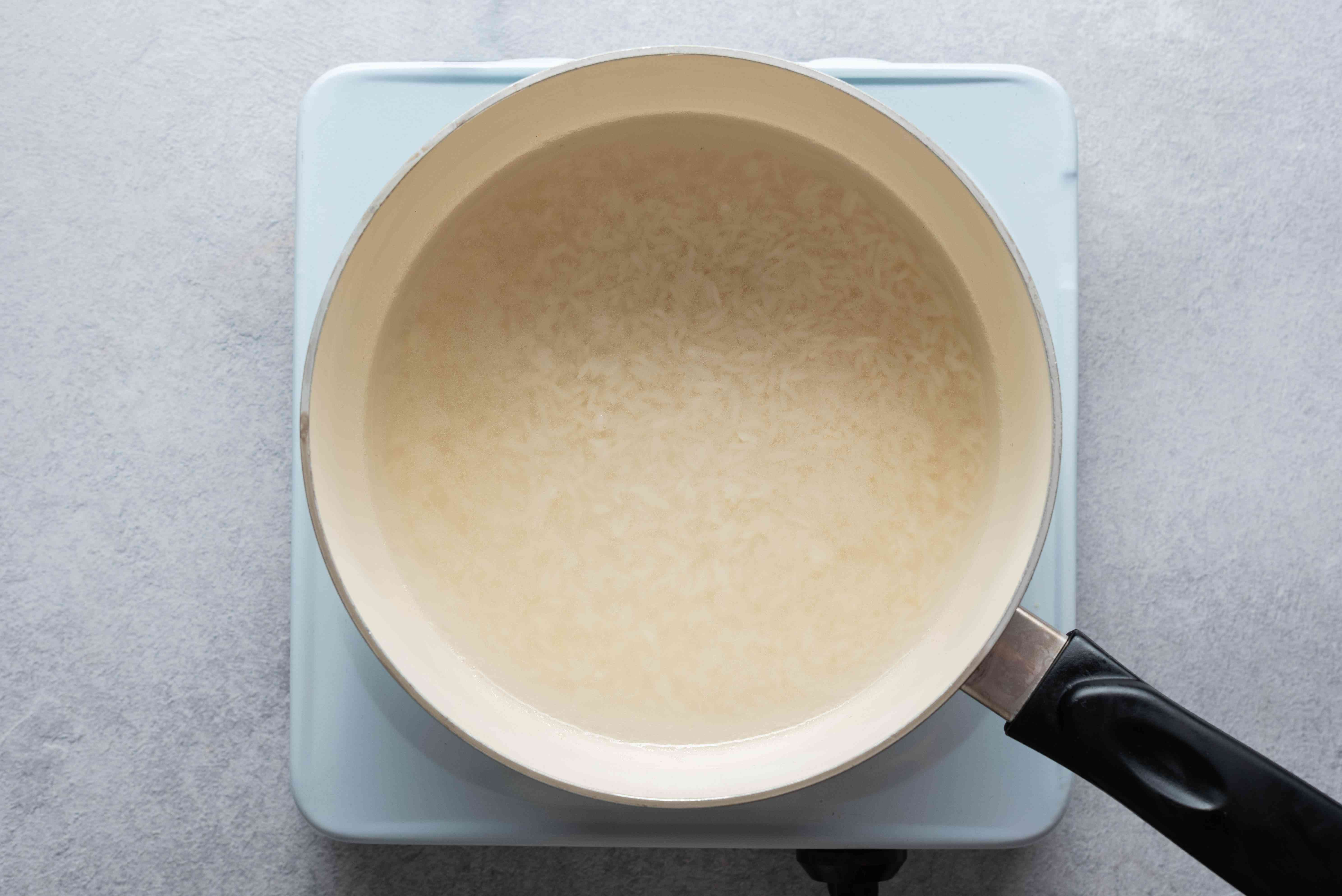 Rice and water cooking in a saucepan