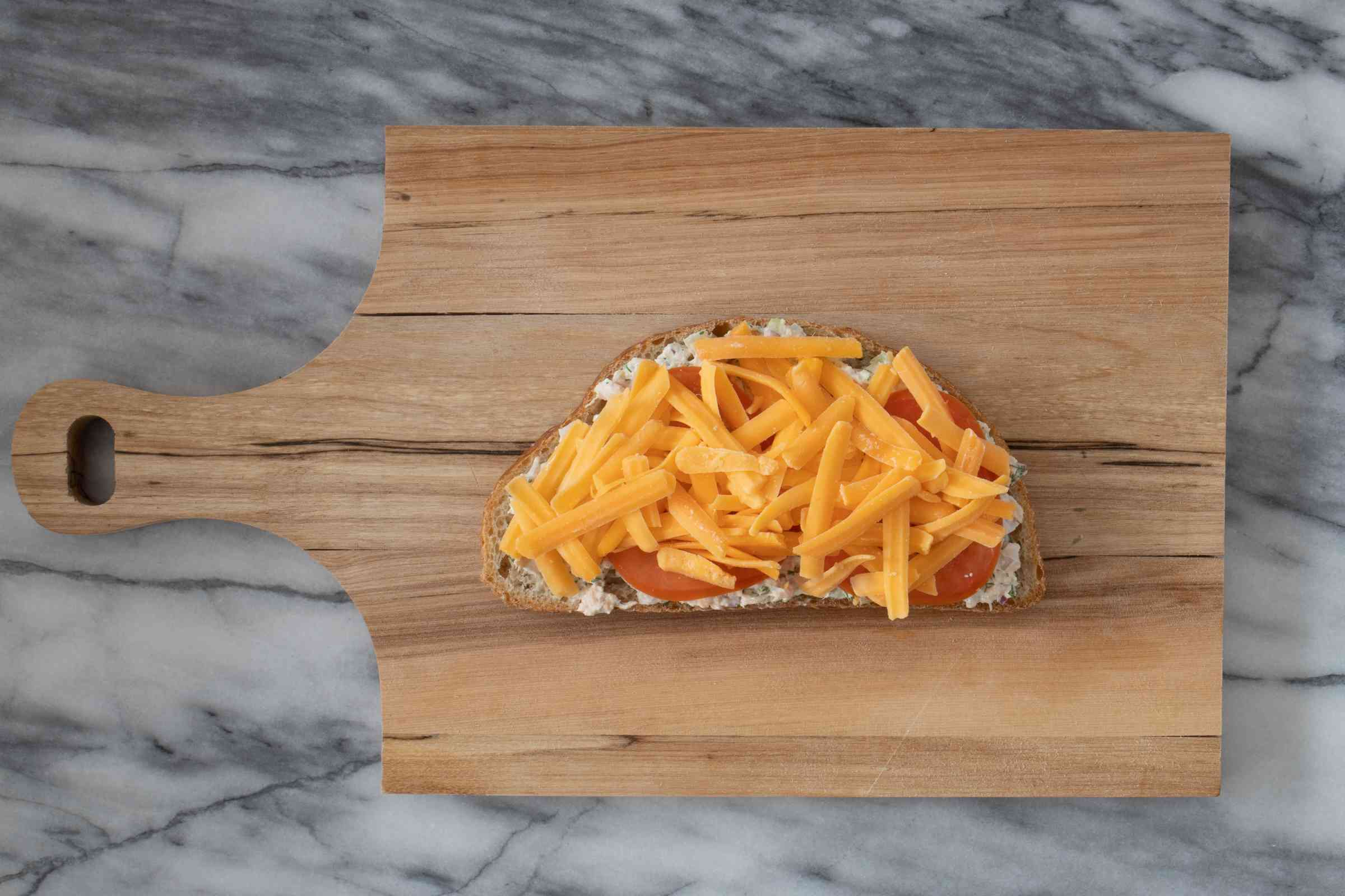 layering tomato and cheese on the tuna melt sandwich
