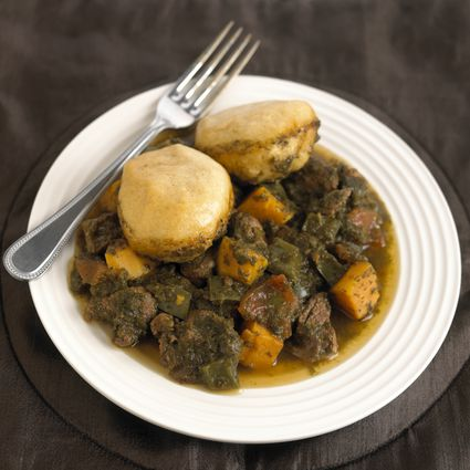 Jamaican pepperpot with dumplings on white plate