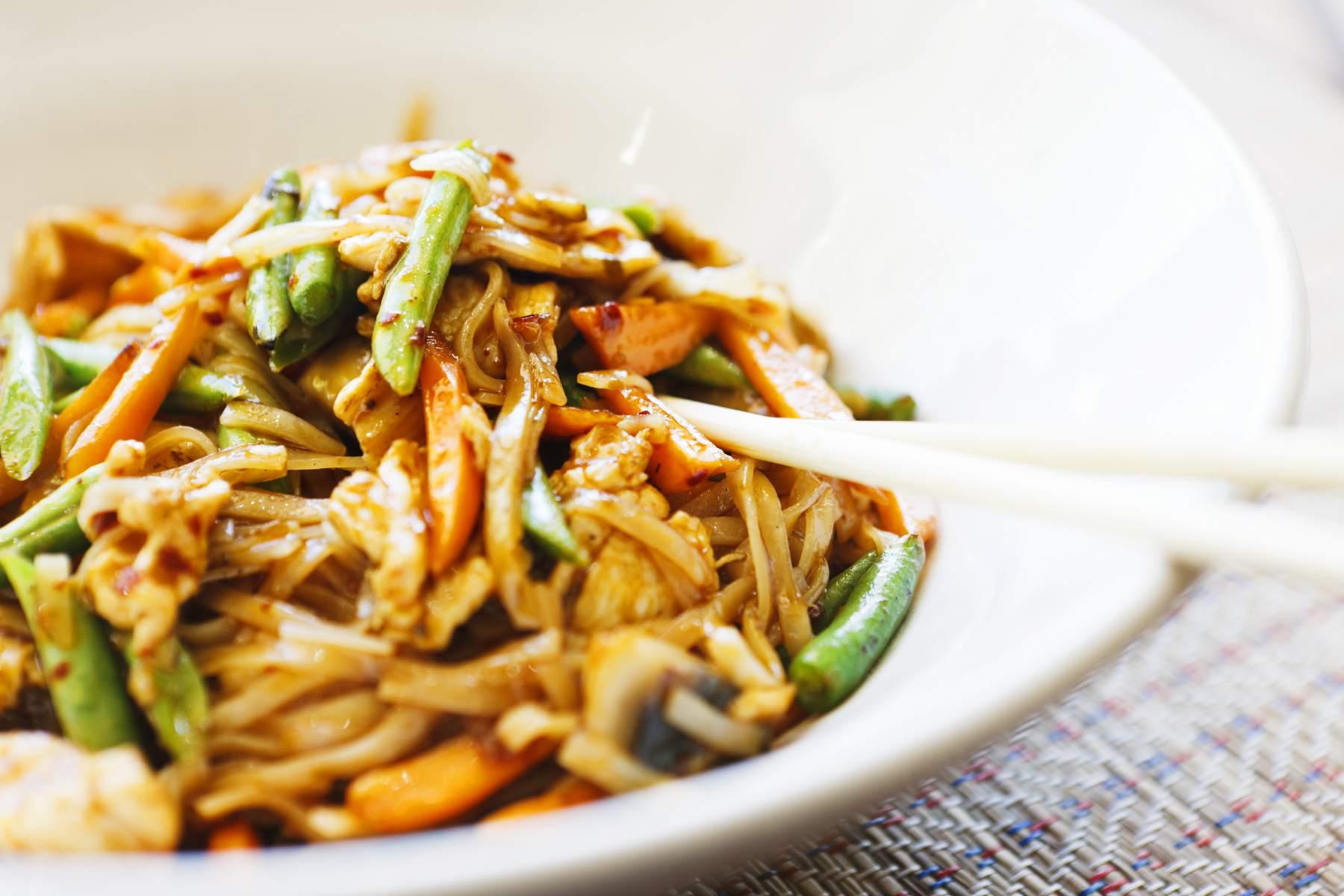 Close up of stir-fried Thai chicken in bowl plus chopsticks