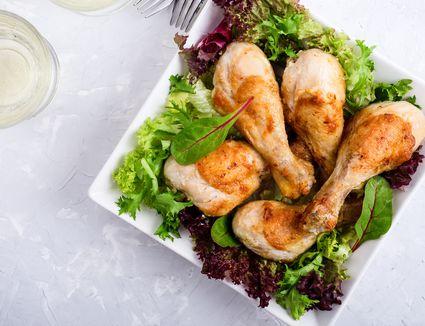 Roast chicken legs on white plate over light gray table