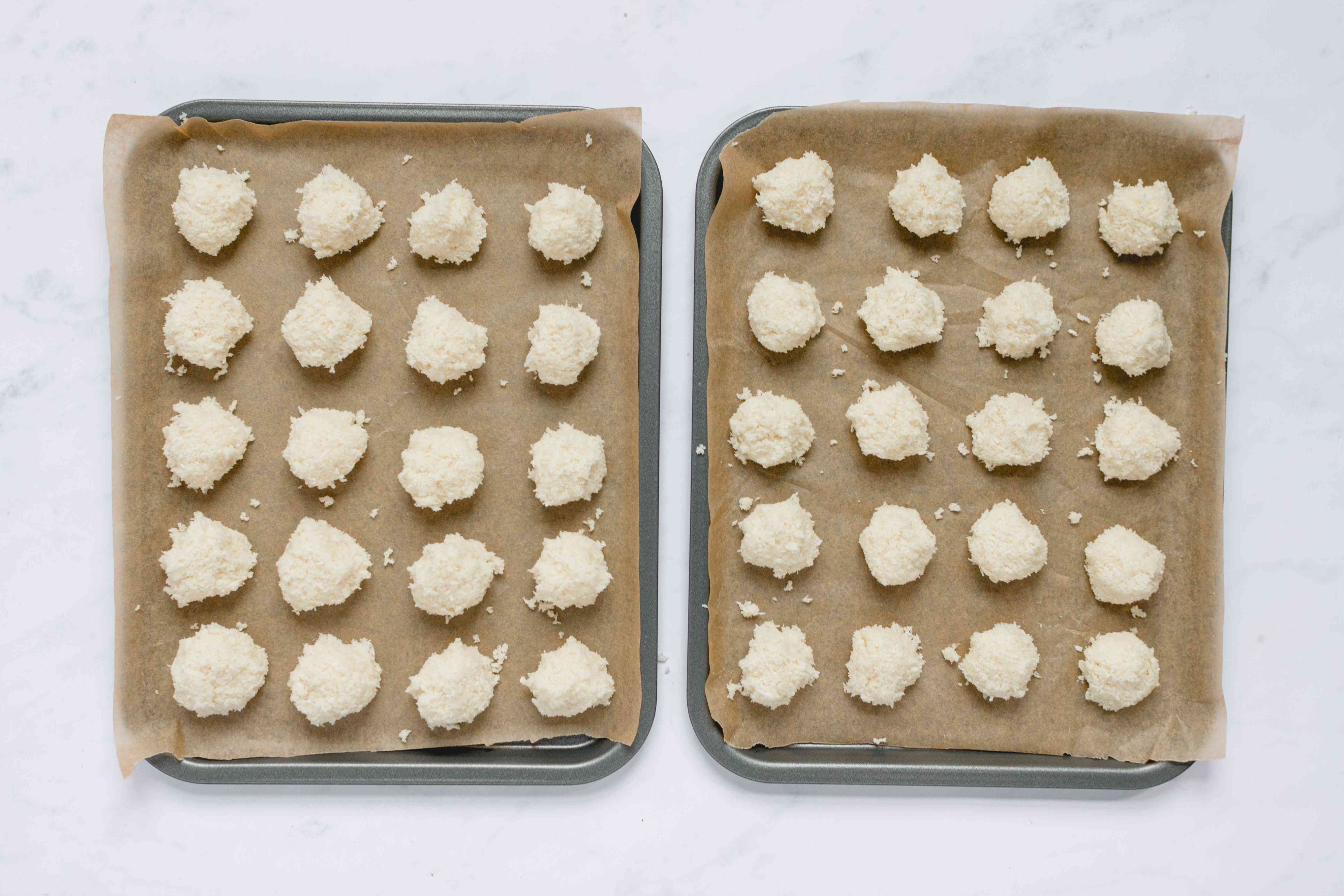 mounds of coconut macaron mixture on baking sheets ready for oven