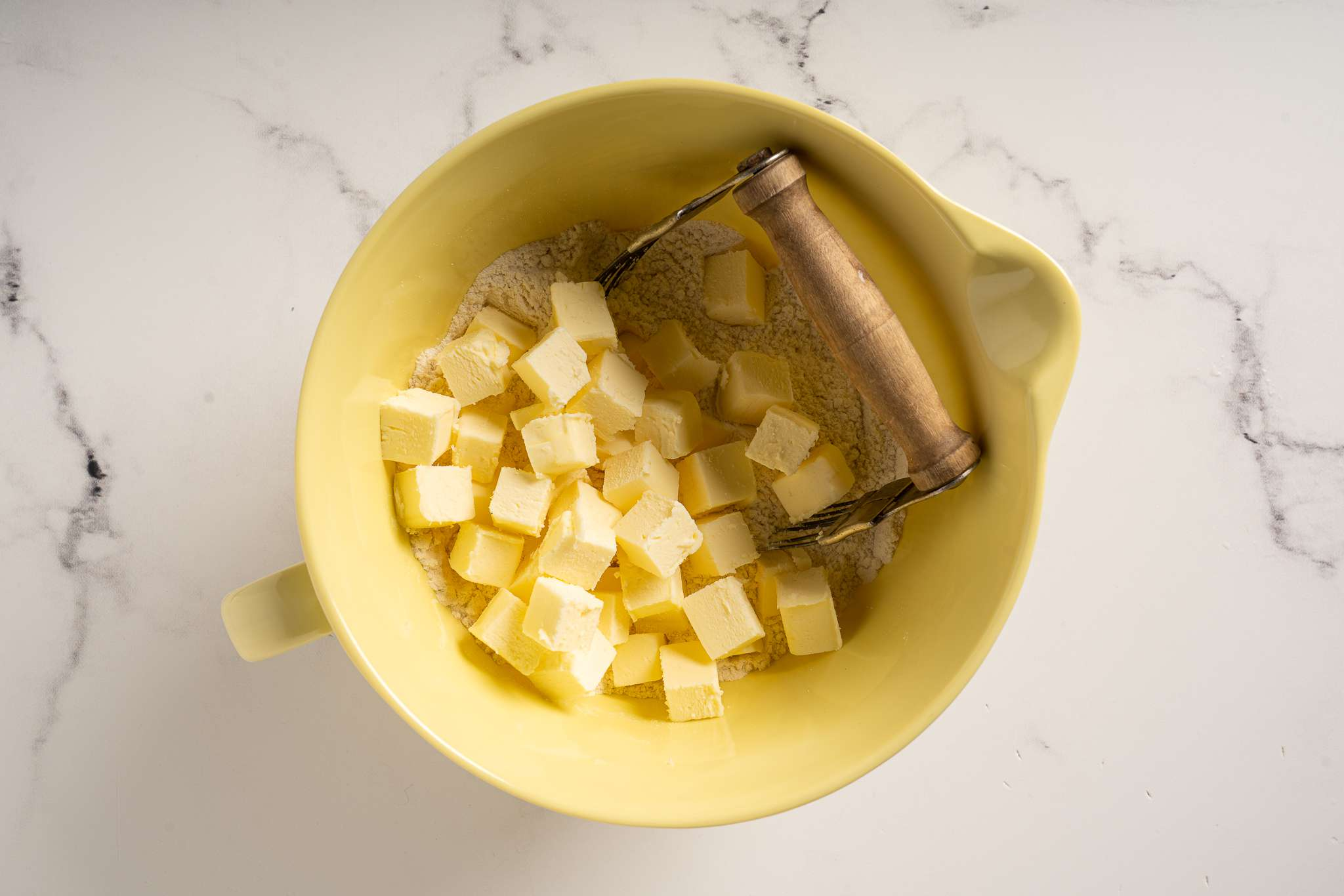 Butter being cut into the dry ingredients in a bowl with a pastry blender