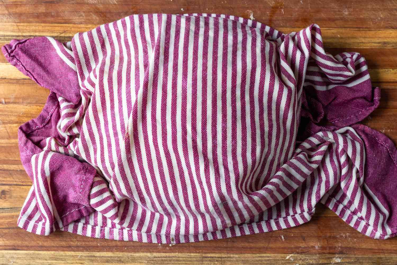 Pan de muerto dough rising under a dish towel
