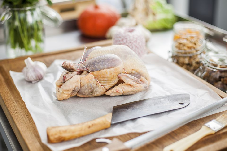 Uncooked filled chicken on chopping board