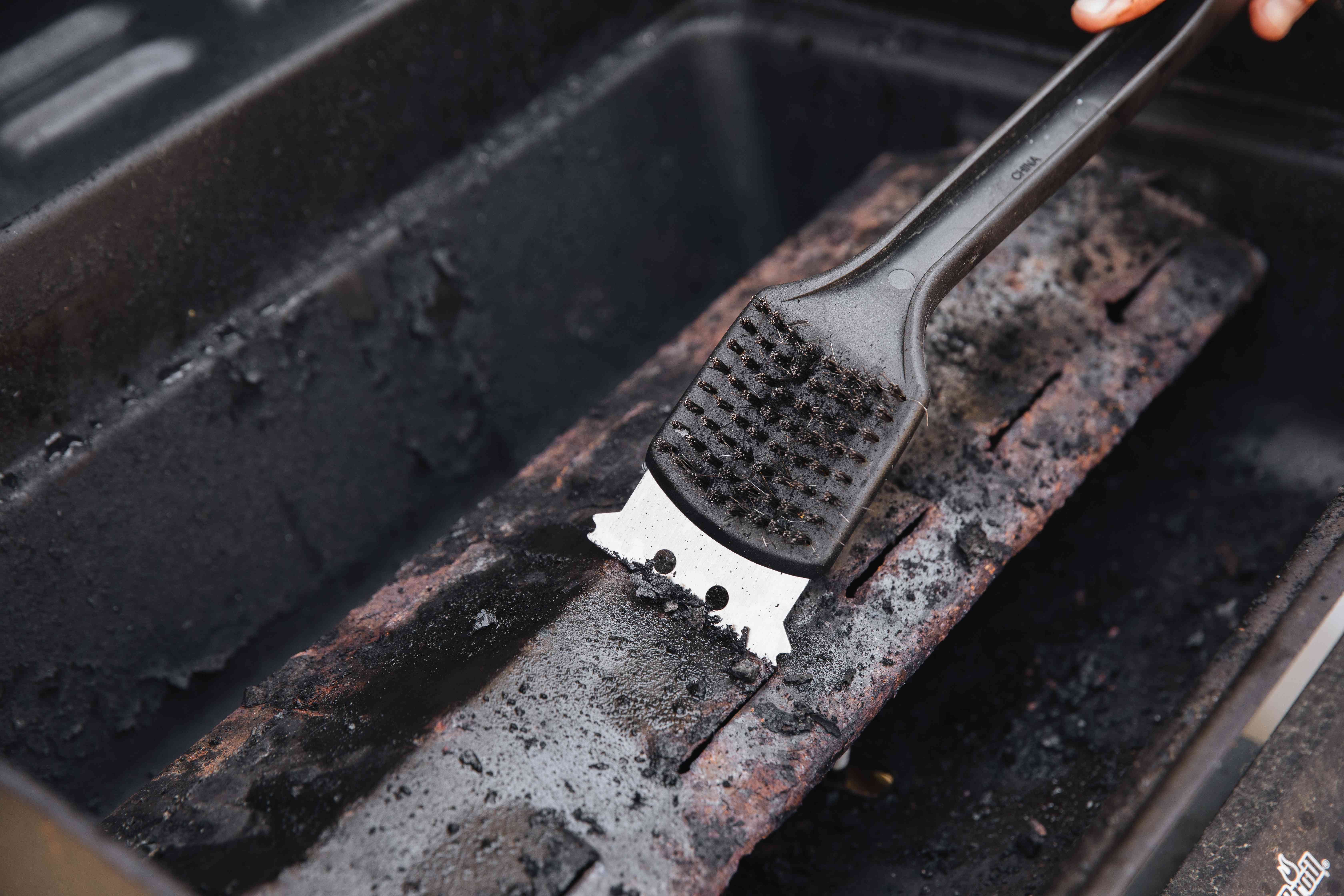 scraping ashes off of the grill