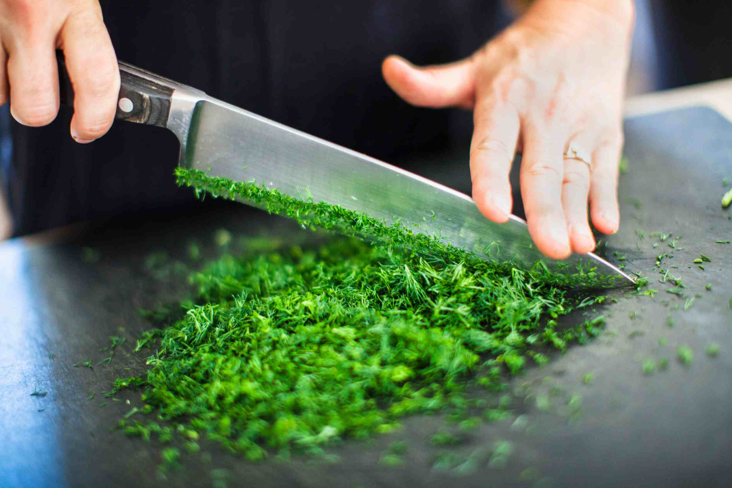 Using a chef's knife to chop fresh herbs