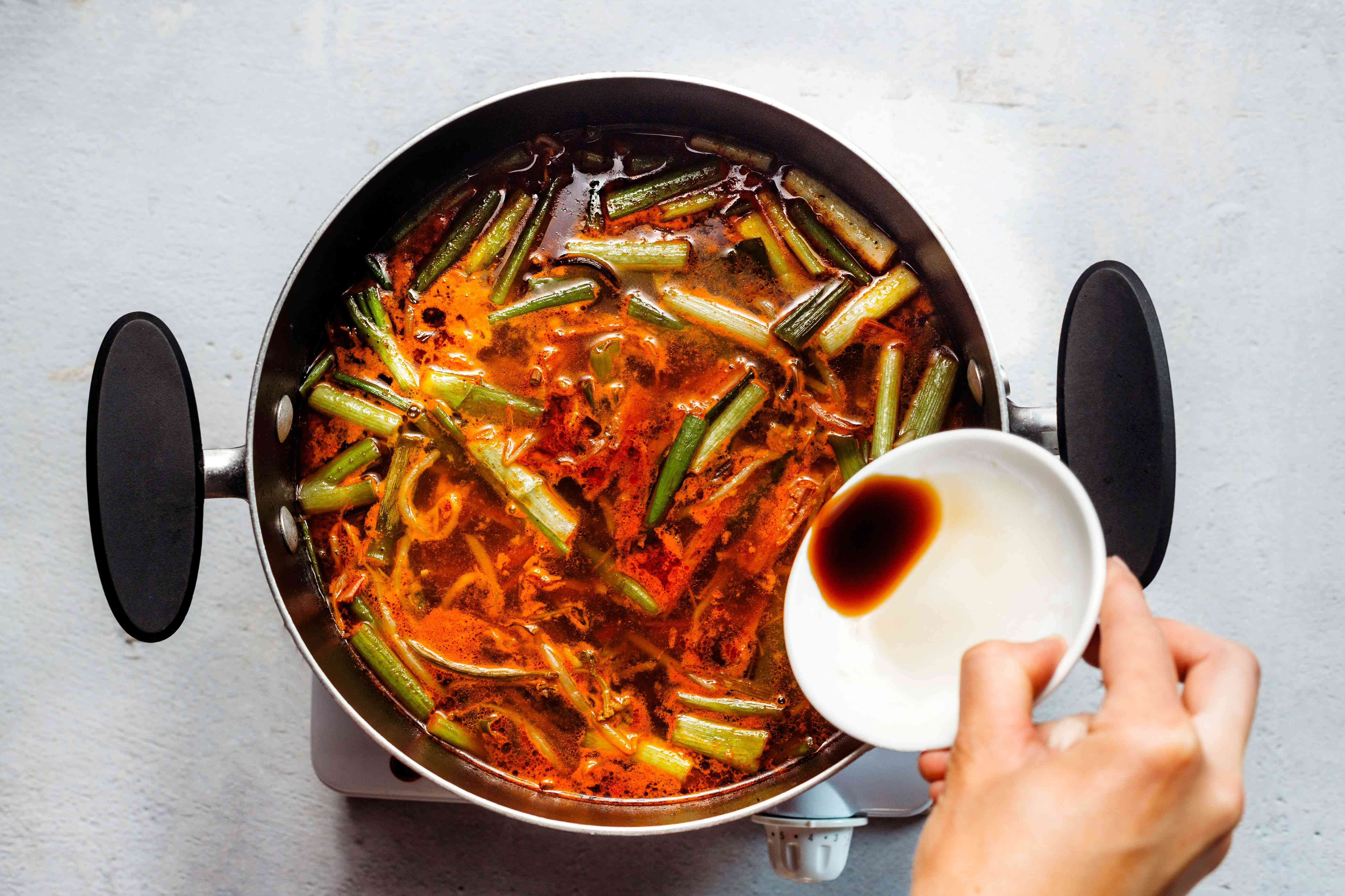 Adding soy sauce to the boiling soup