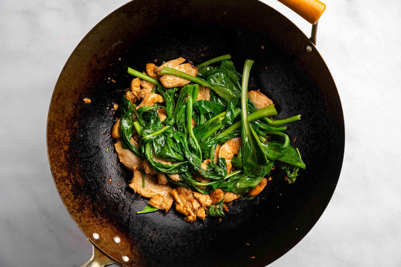 Add vegetables to chicken in wok