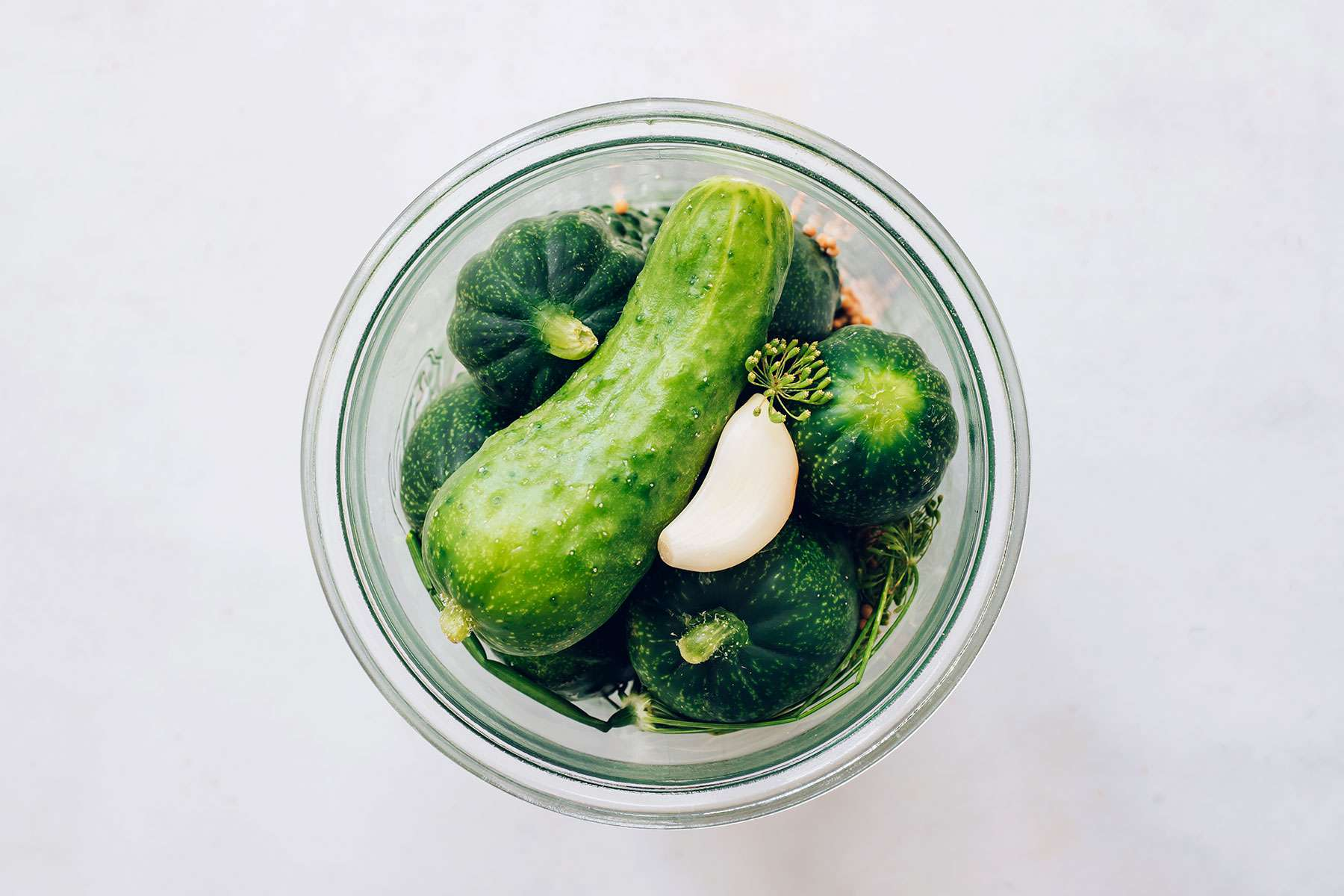Place mustard seeds, garlic, and dill in a jar