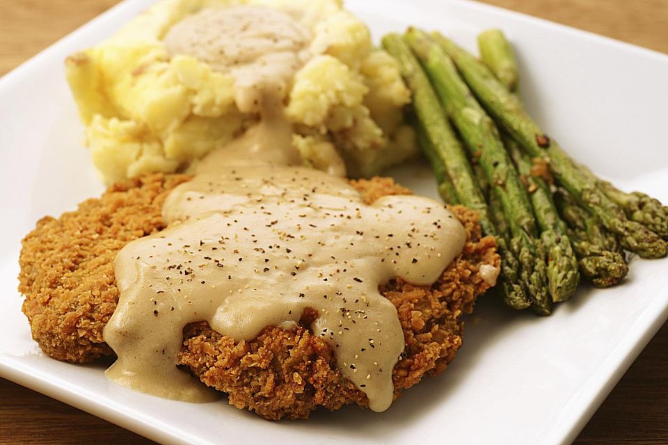 A plate of country-fried steak with gravy and sides