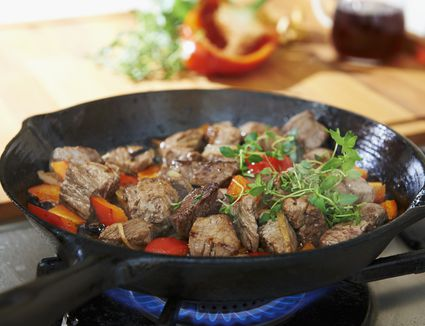 Pan frying meat and vegetables on the stove