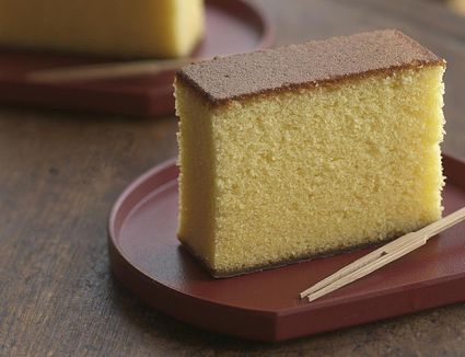 Pieces of yellow cake on wooden round table