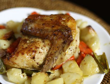 Roasted chicken with potatoes and carrots on a white plate