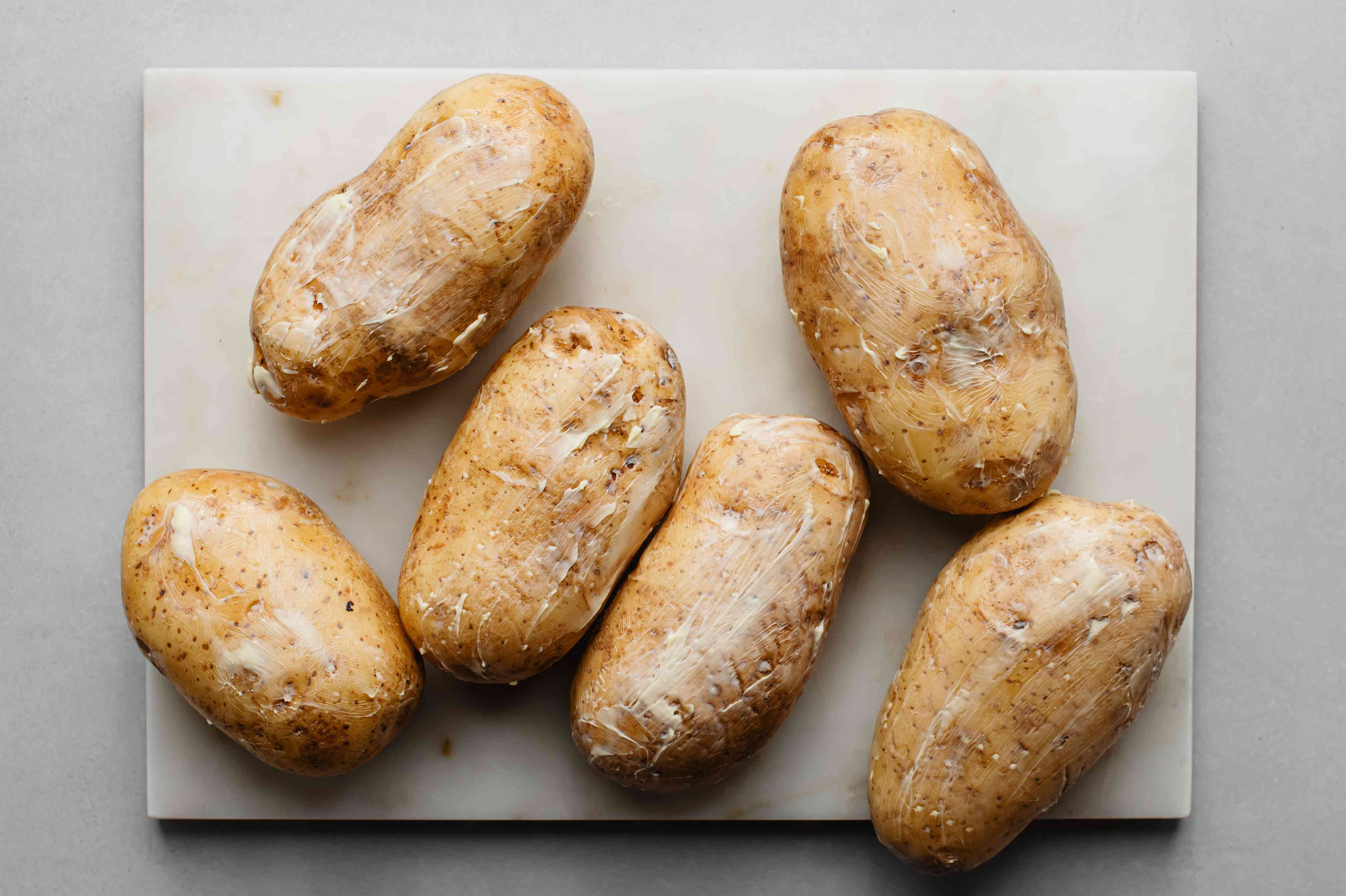 Rub the potatoes with softened butter