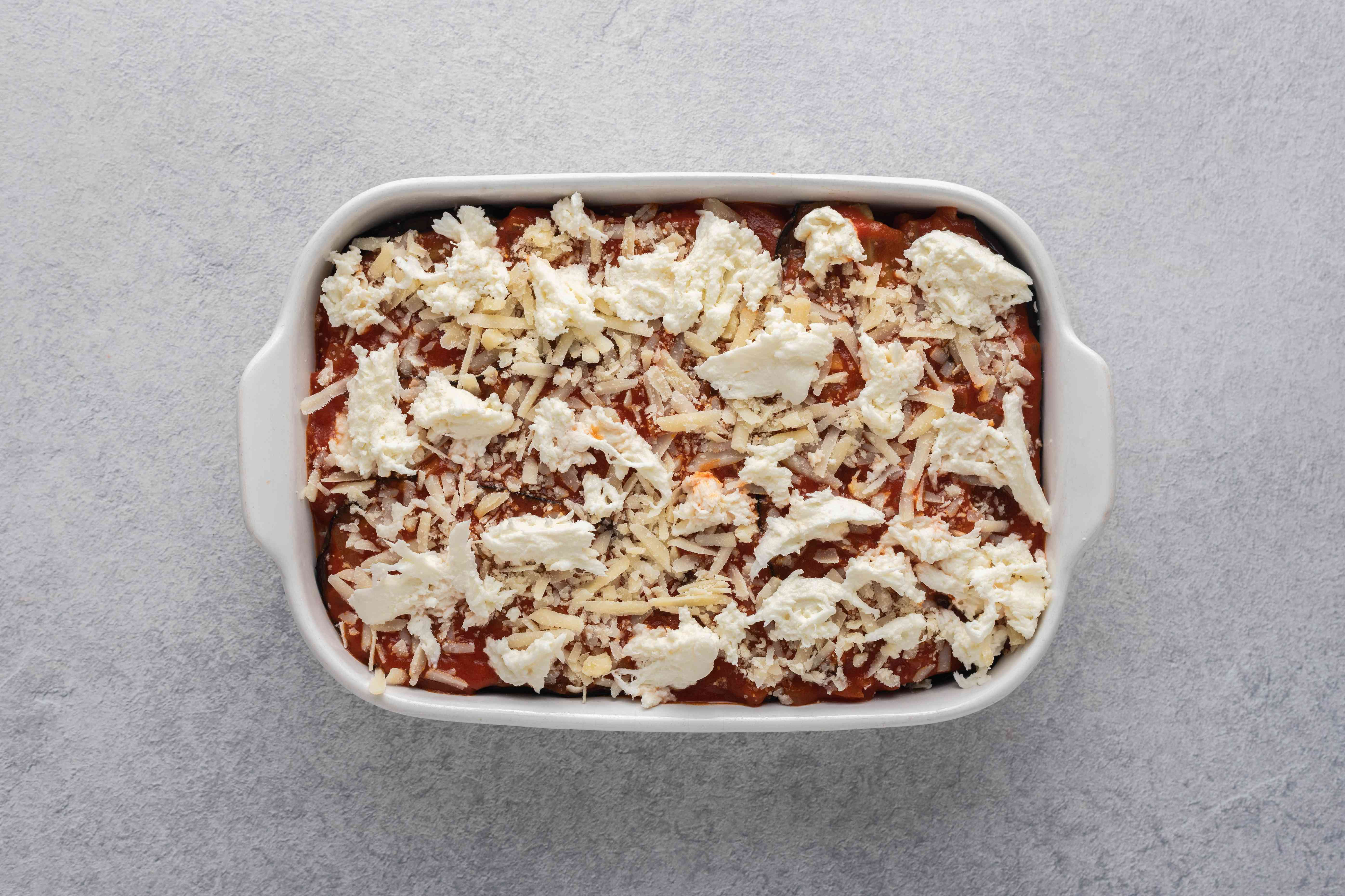 cheese on top of eggplant parmesan in a baking dish
