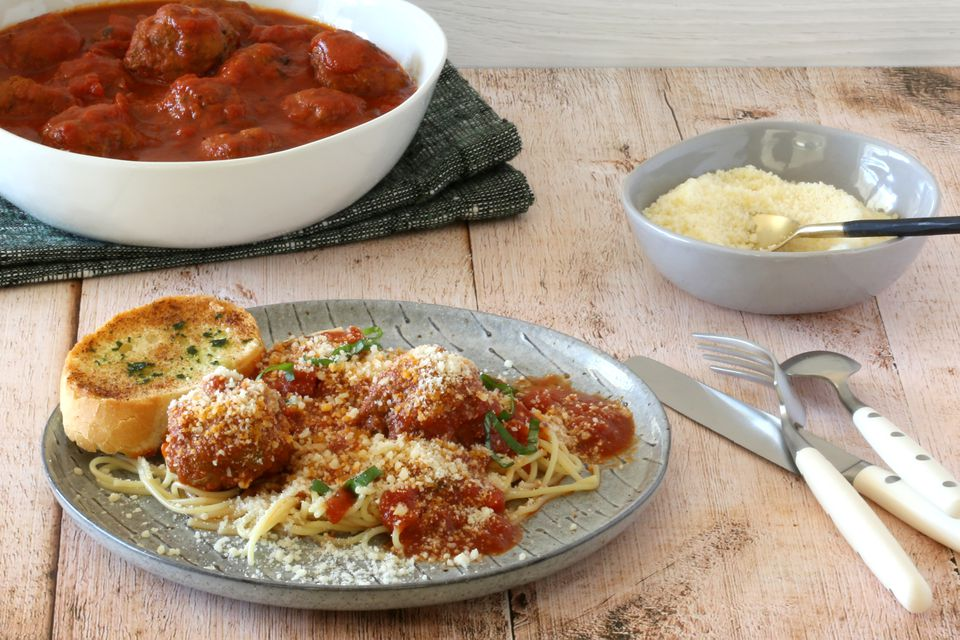 Spaghetti and meatball dinner with Parmesan cheese.
