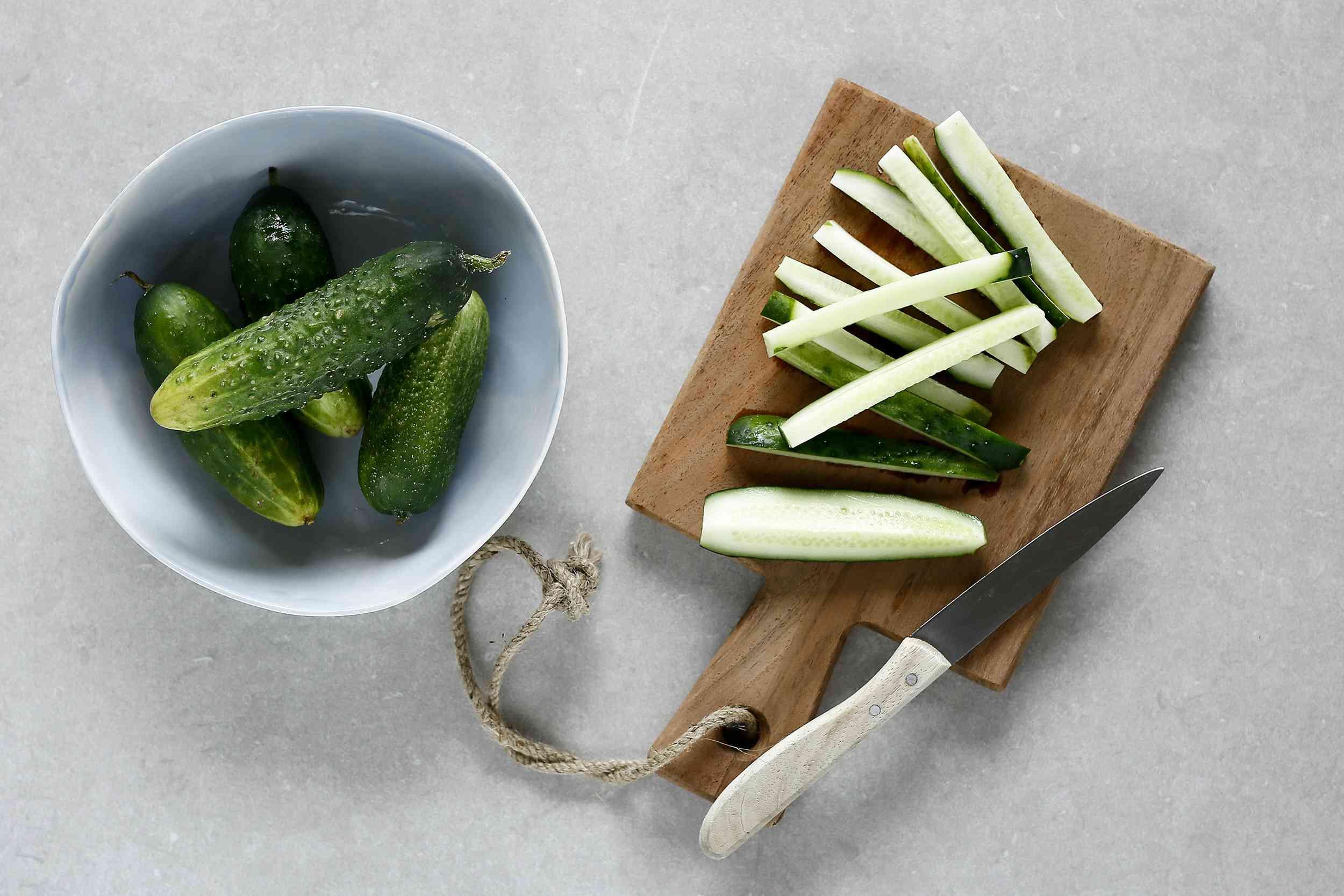 cucumbers cut into strips on a wood cutting board