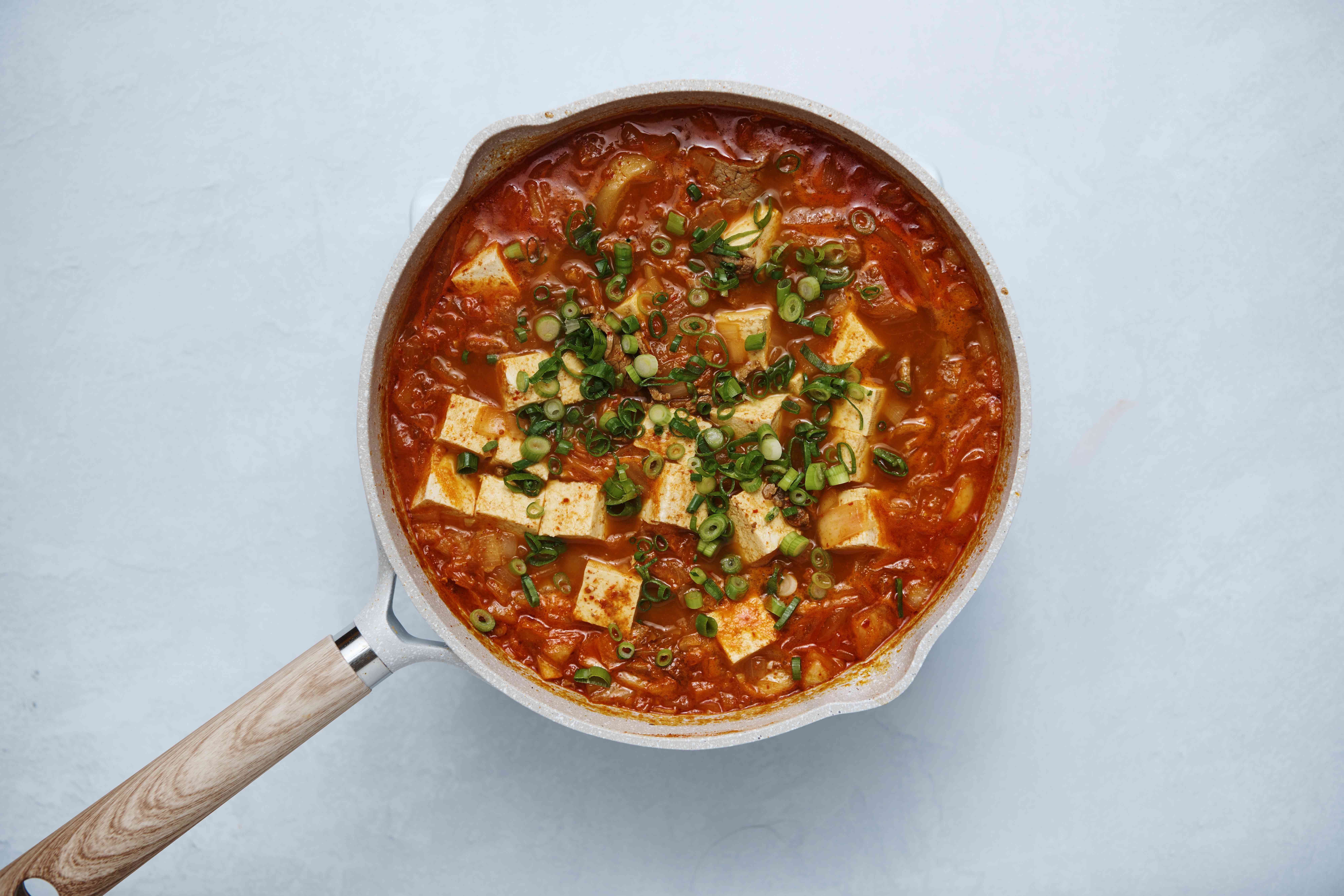 Scallions are added to the kimchi stew