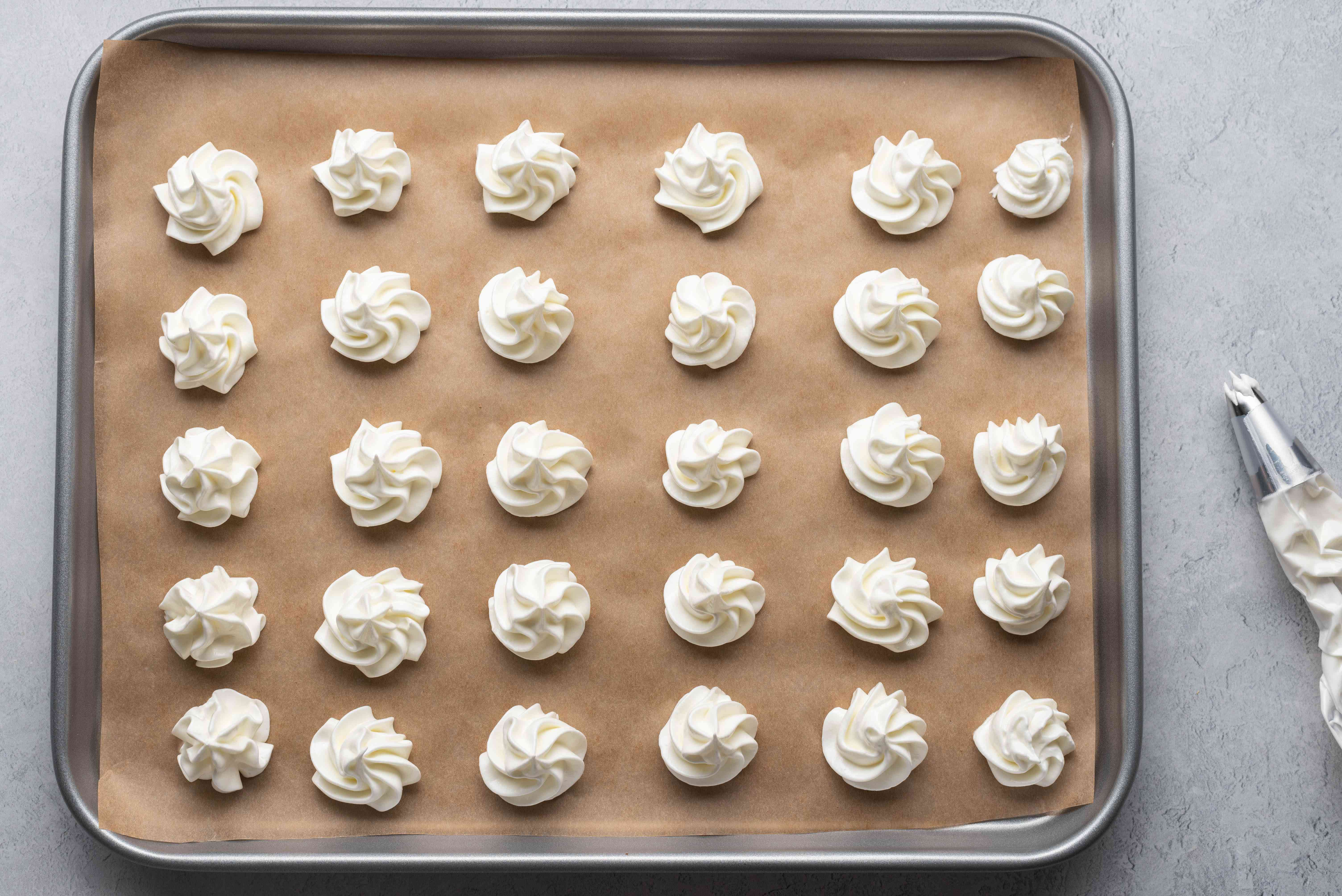 A baking sheet with piped meringue swirls