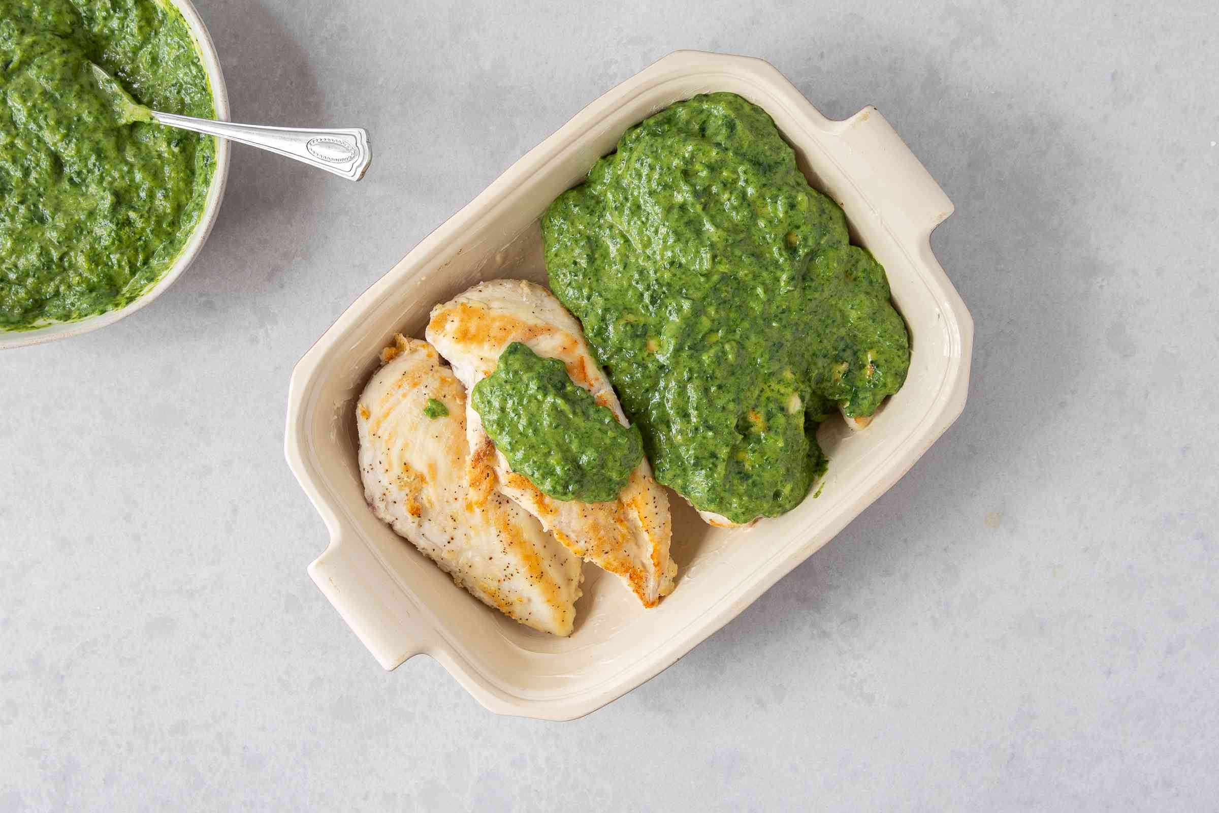 chicken in a baking dish, covered with spinach soufflé