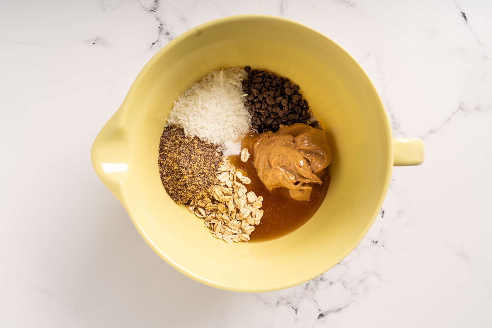 Combine oats, coconut flakes, peanut butter, honey, chocolate chips, flax seed, vanilla extract, and salt in a large bowl