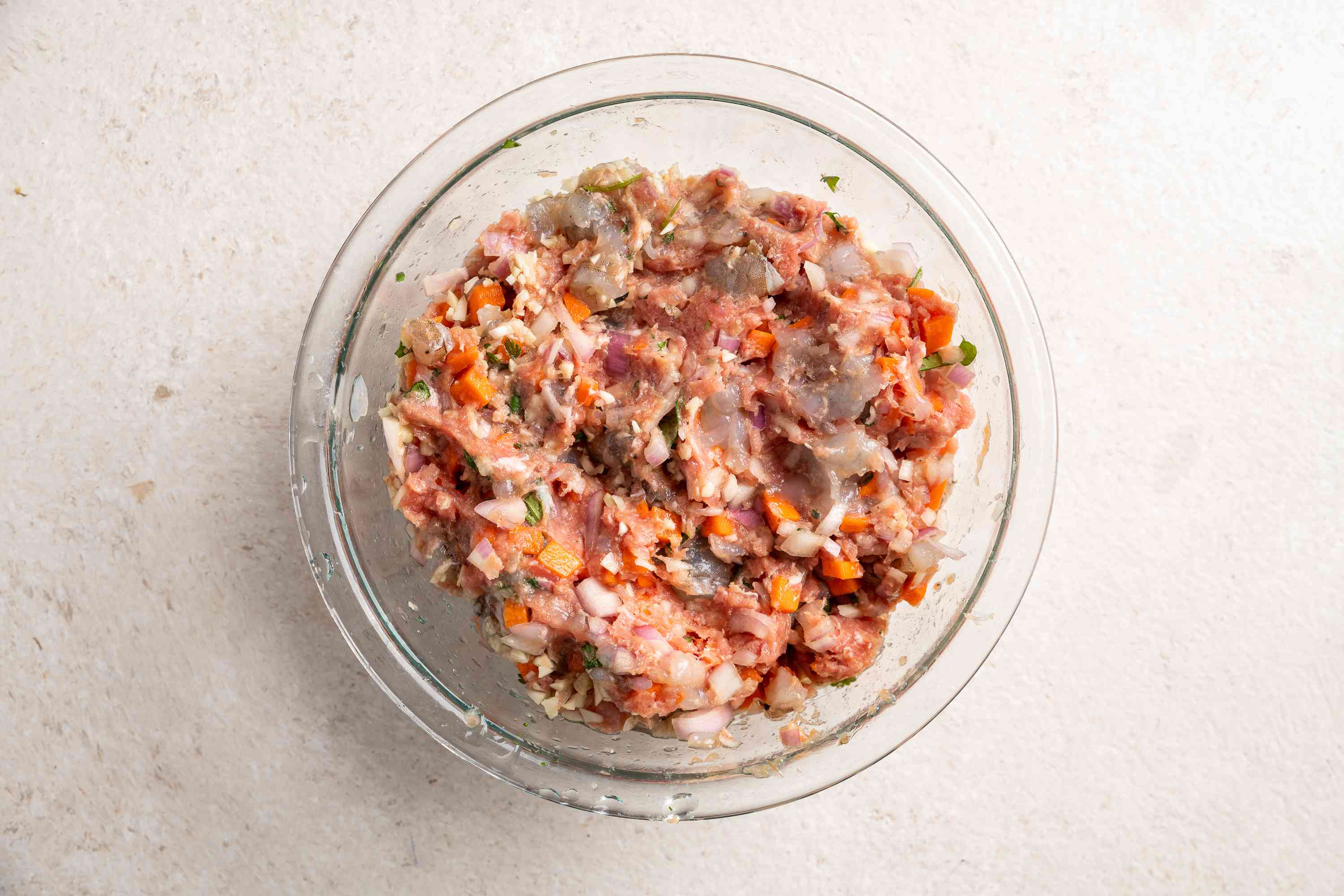 Place the ground pork and minced shrimp in a bowl and add the chopped shallots, carrots, garlic, and cilantro, season with fish sauce