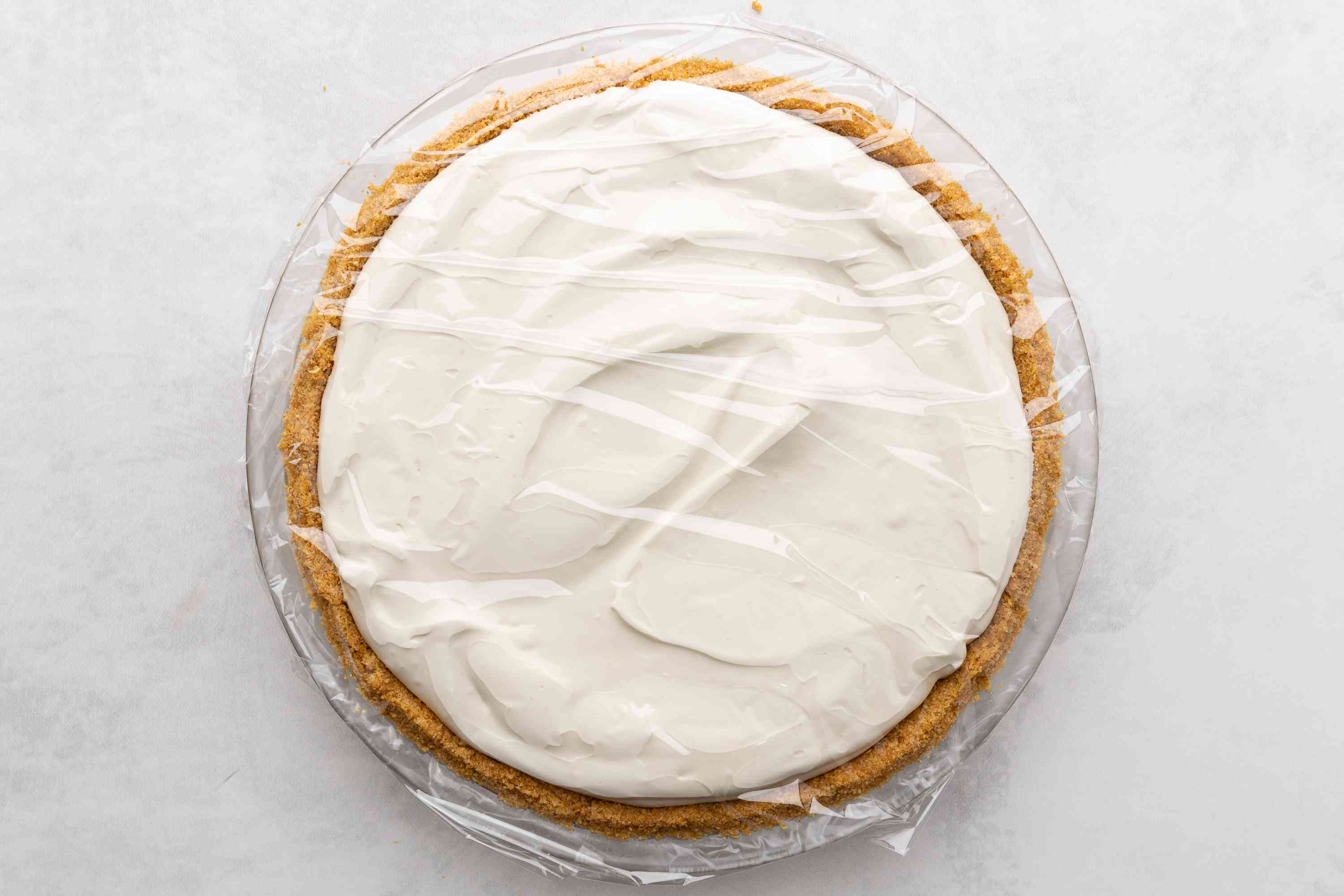add pie filling into the crust and cover with plastic wrap