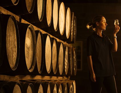 Female taster looking at the colour of whisky in glass at whisky distillery