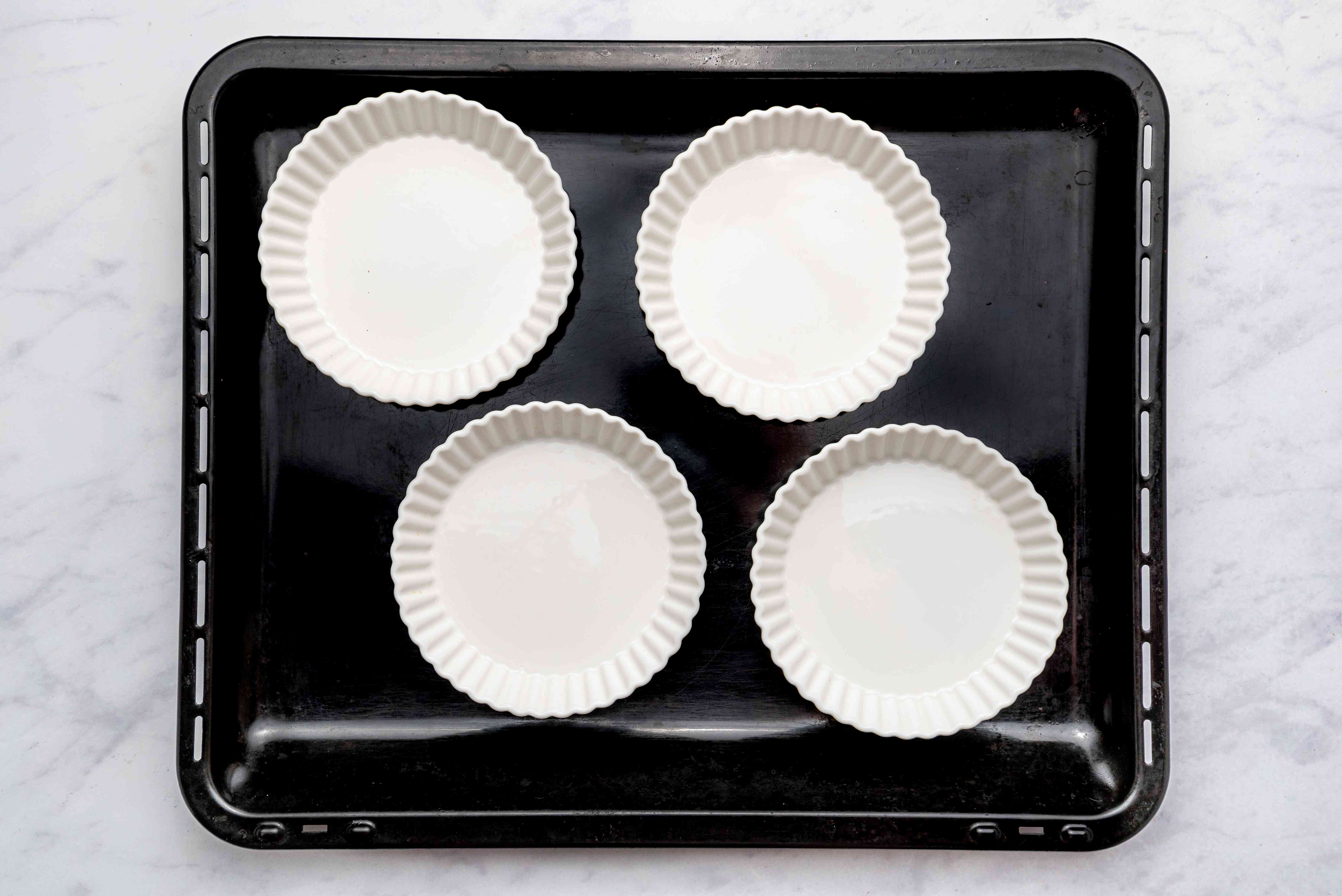 four 6-ounce custard cups in a larger baking pan