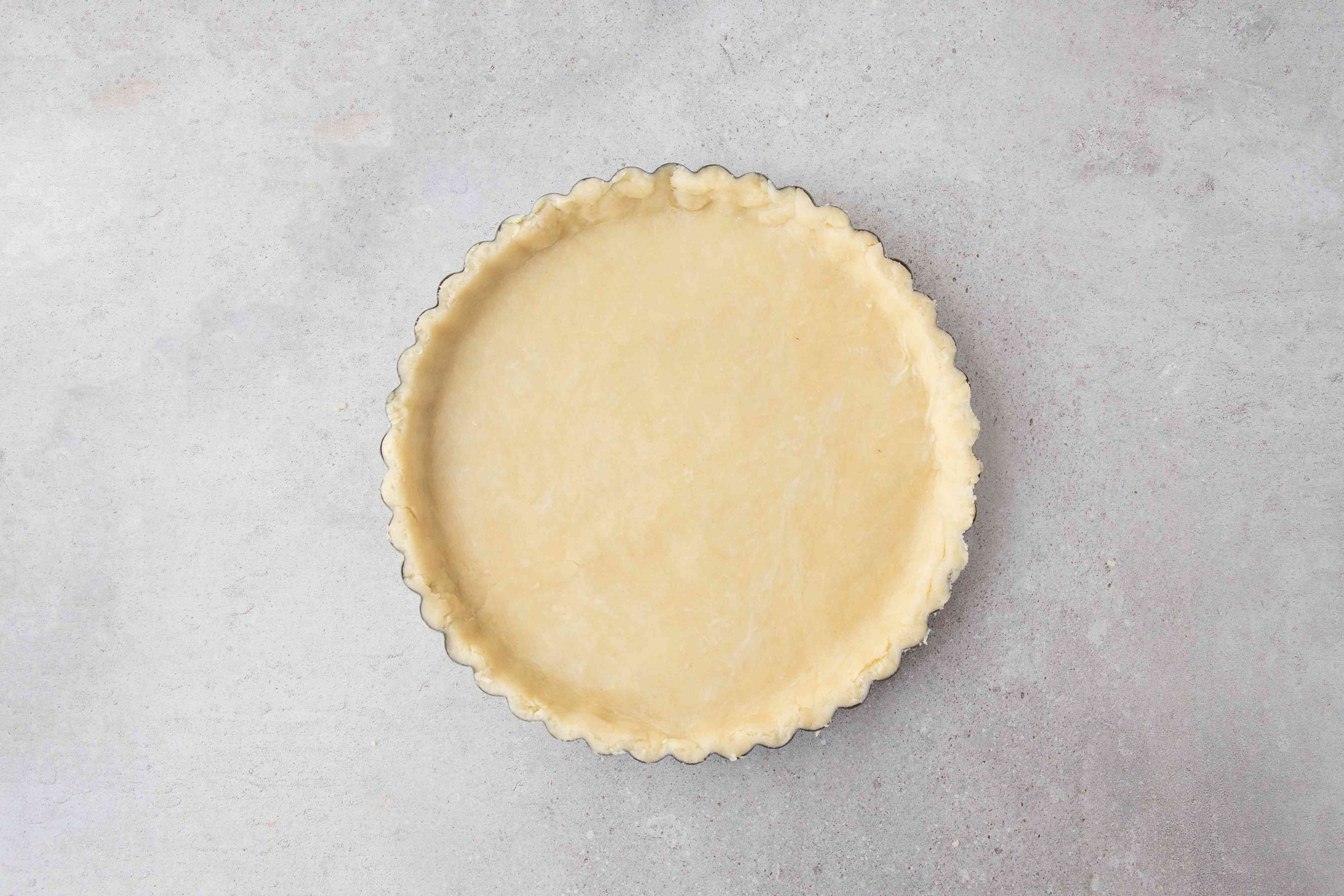 Dough with crimped edges in a pastry tin