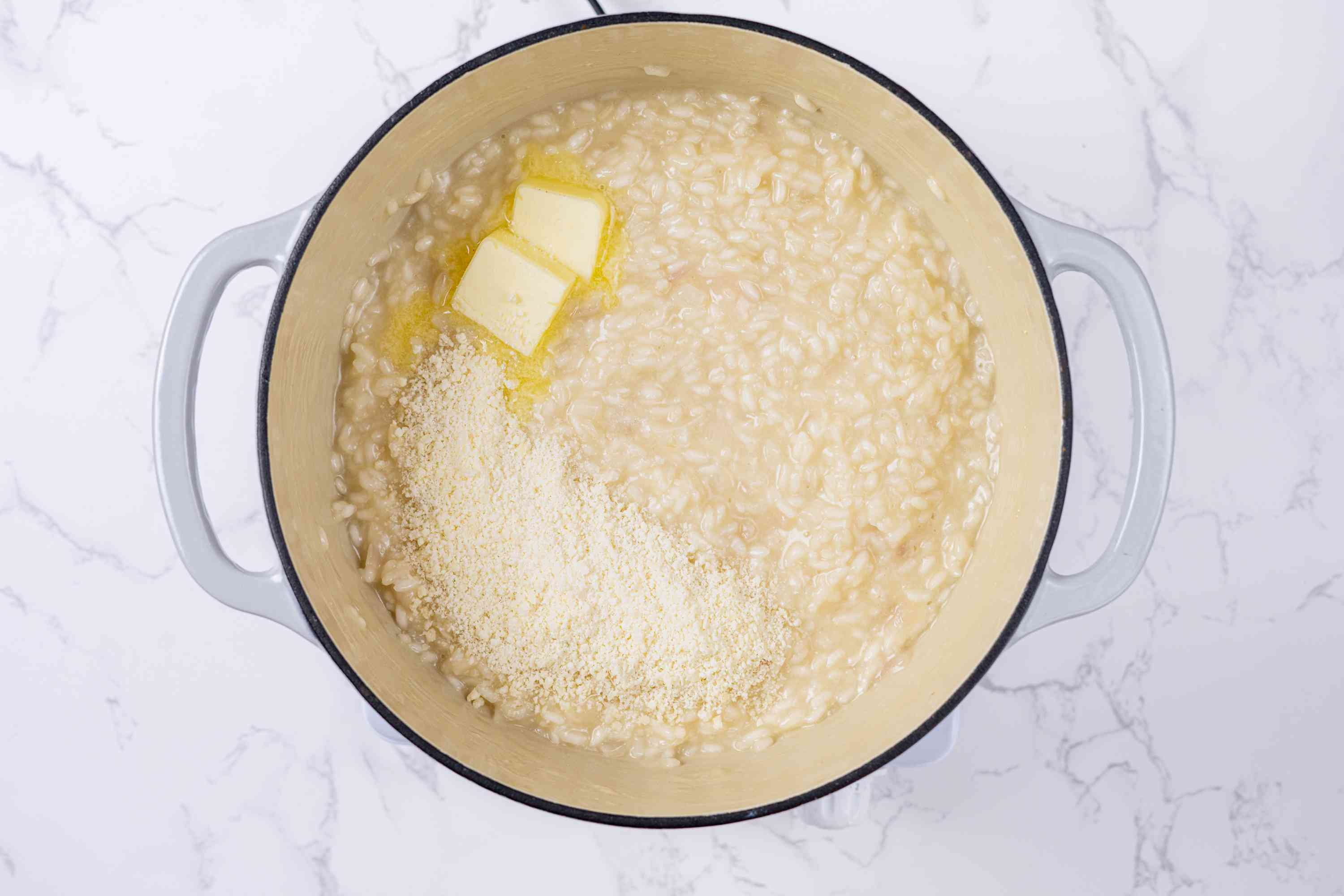 butter and the Parmesan cheese added to the risotto in the pot