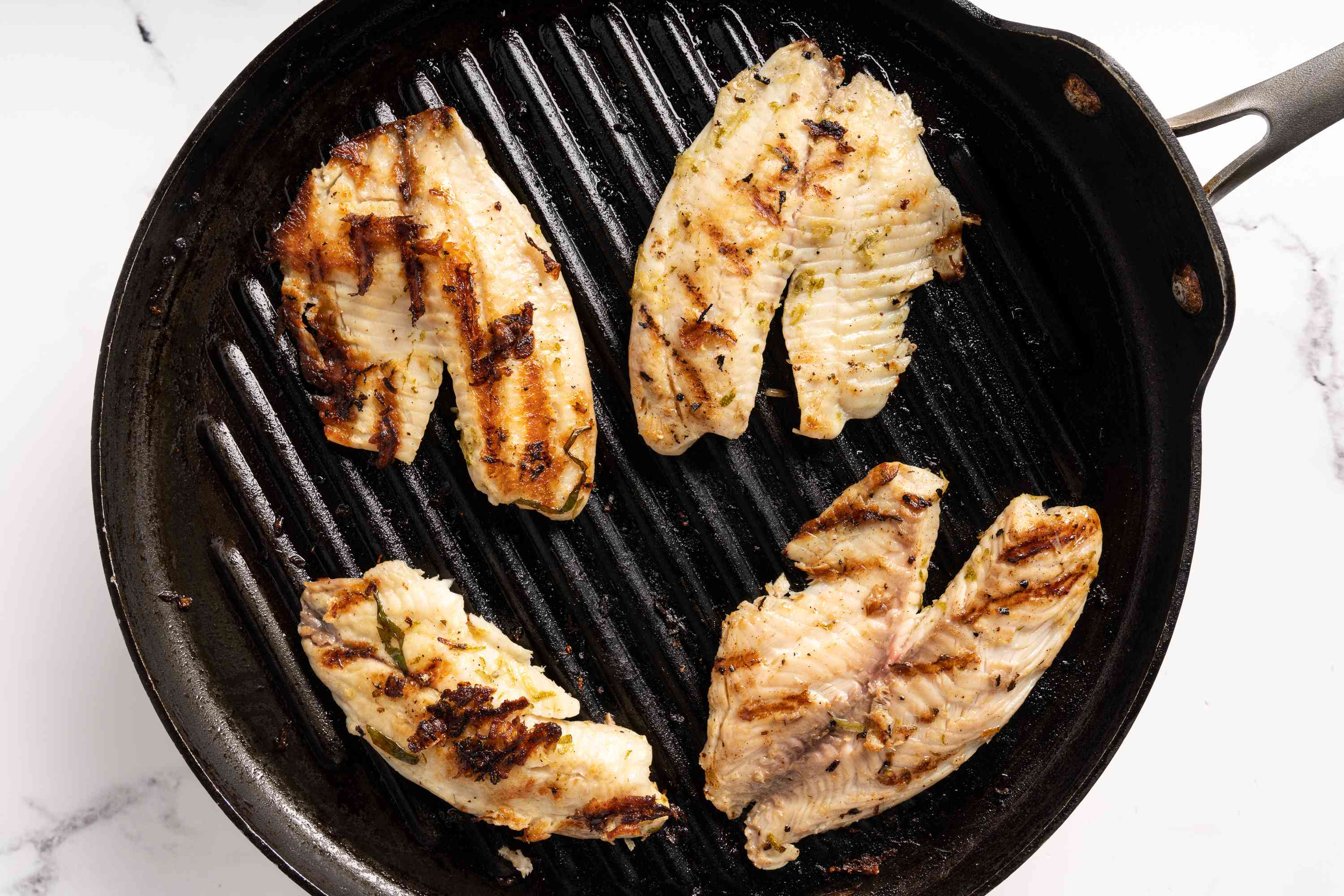 tilapia cooking on a grill pan