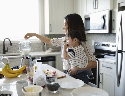 Mother holding baby daughter, blending smoothie in kitchen