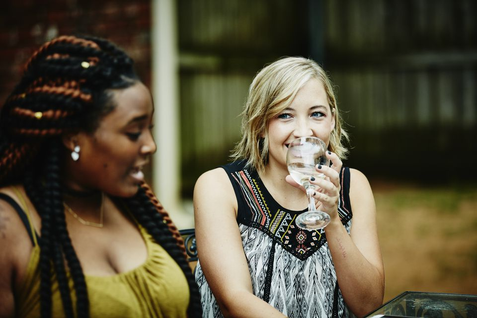 Smiling woman sharing wine with friends