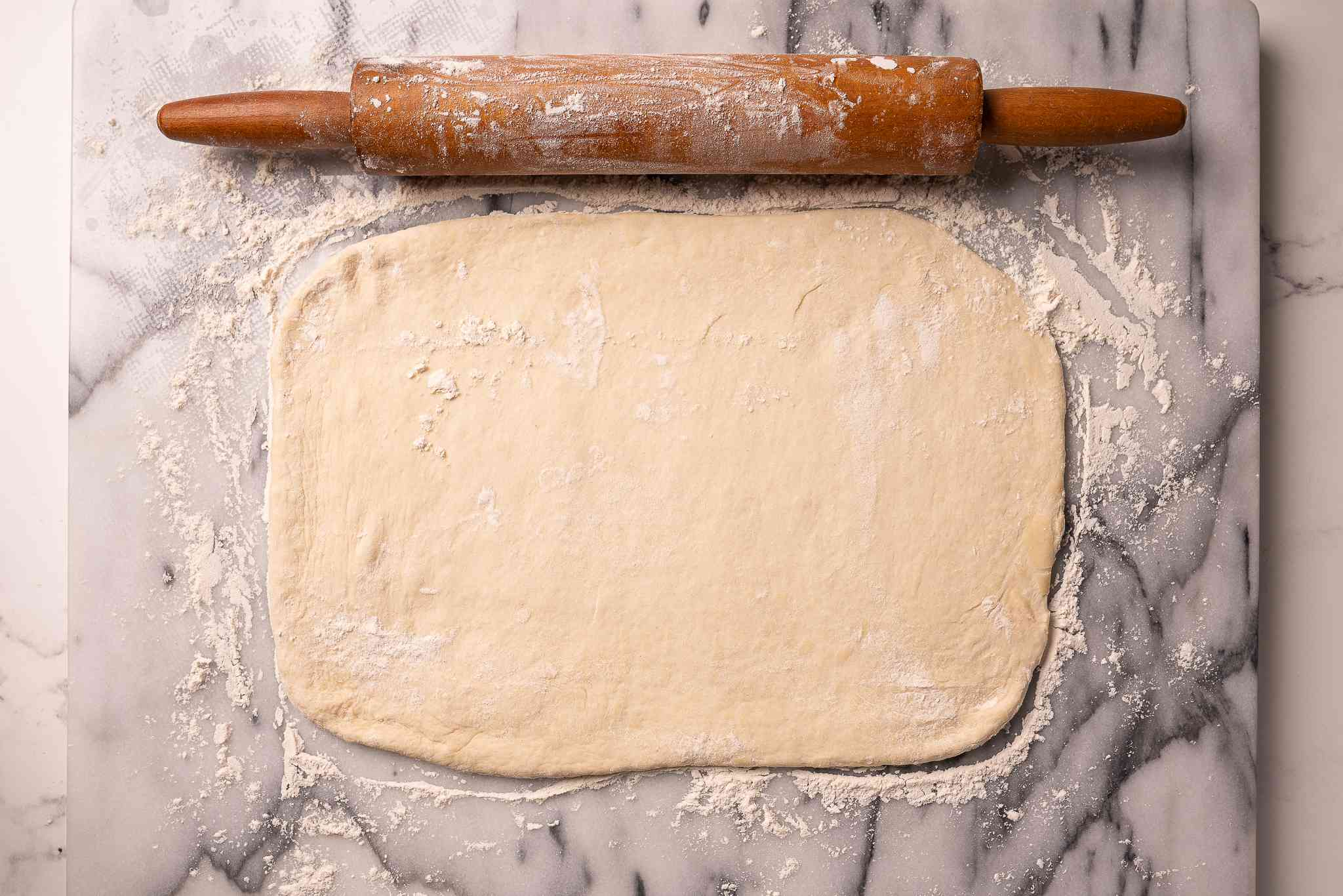 Bread dough rolled out into a rectangle on a floured surface