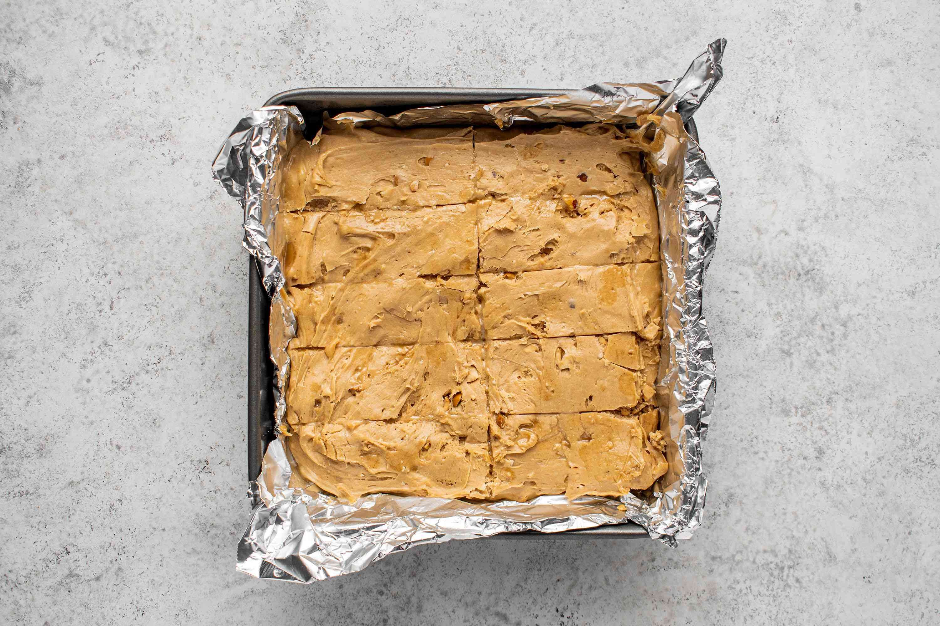 peanut butter mixture cut into pieces in a prepared baking pan