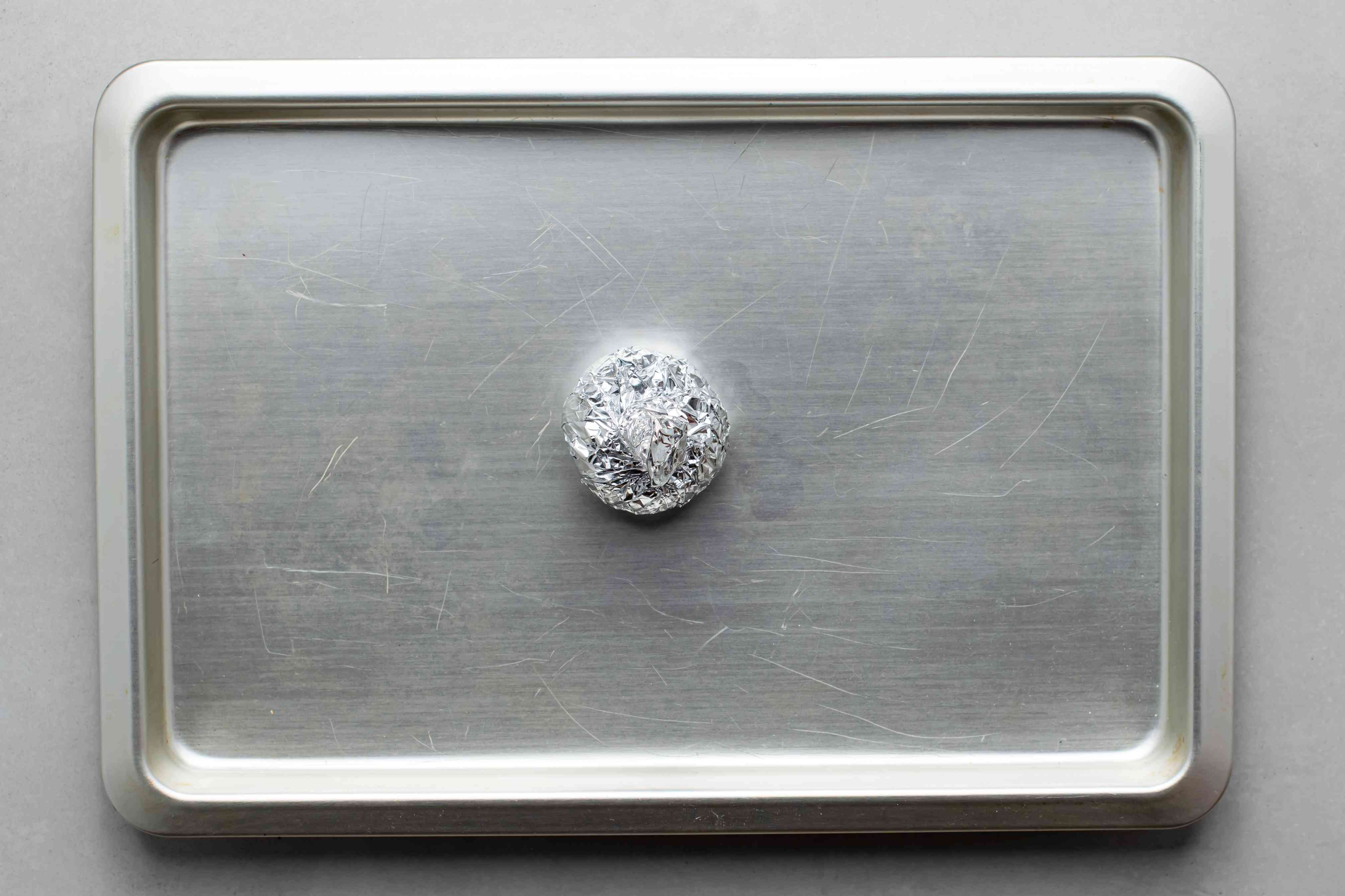 Garlic wrapped with aluminum foil on a baking sheet