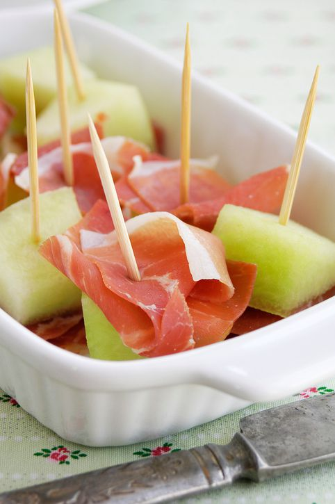 Pieces of jamon and green melon for snack.