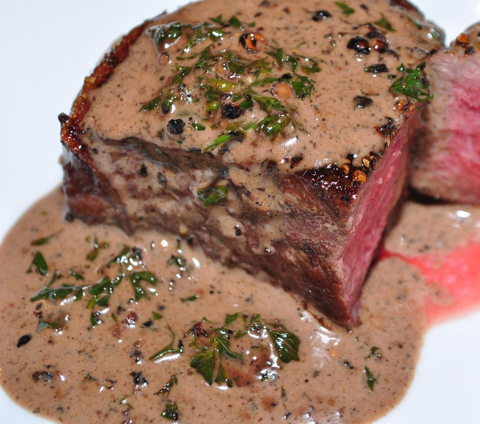 A plate of filet mignon with garlic mustard sauce