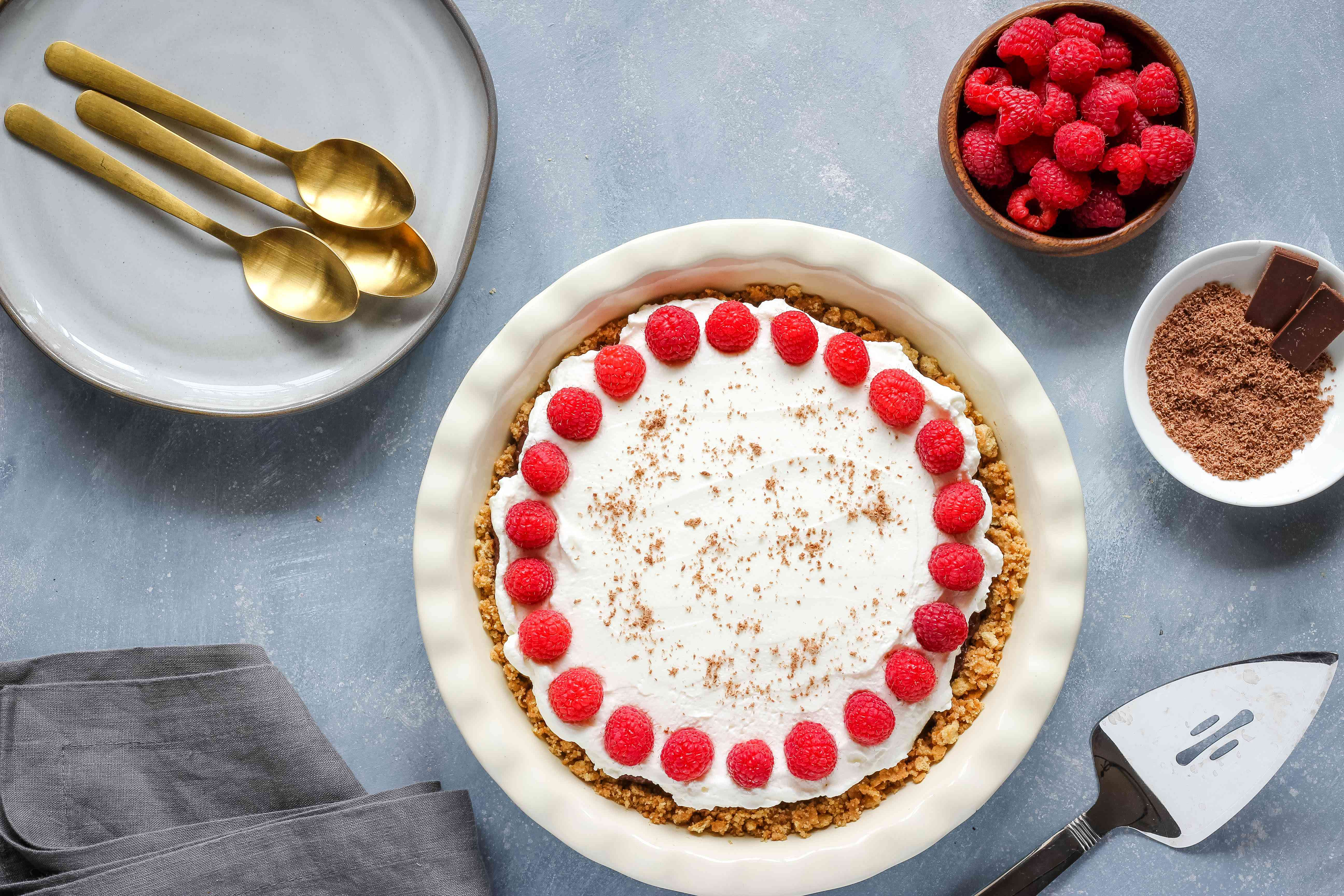 Chocolate pudding pie topped with raspberries and chocolate shavings
