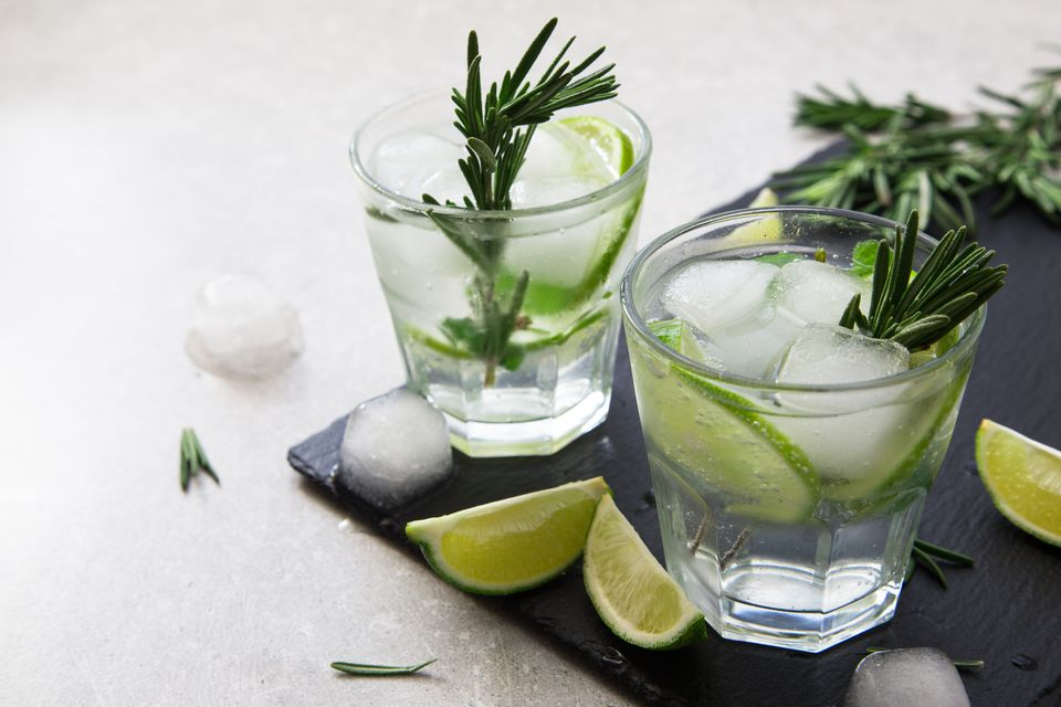 Gin and tonic with lime and rosemary on a slate board