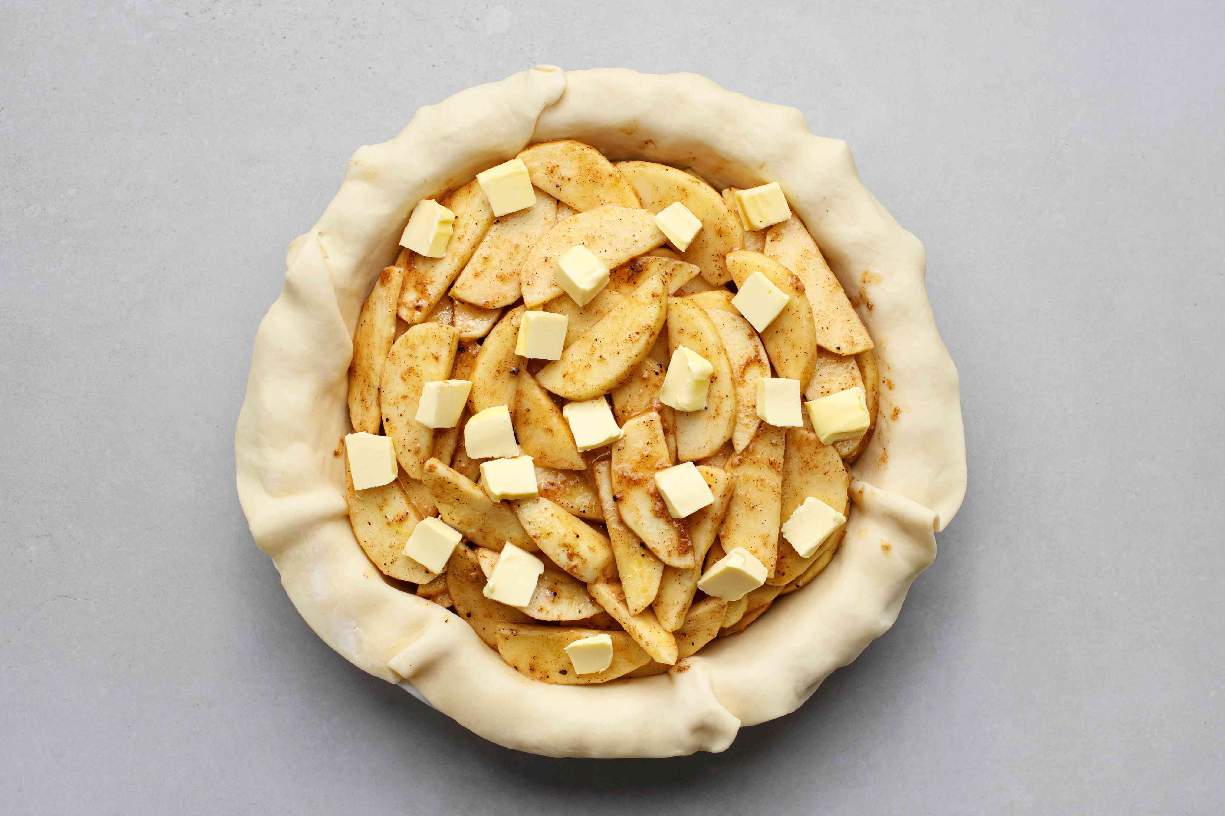 Pour the apple filling into the crust-lined pie pan and dot with butter