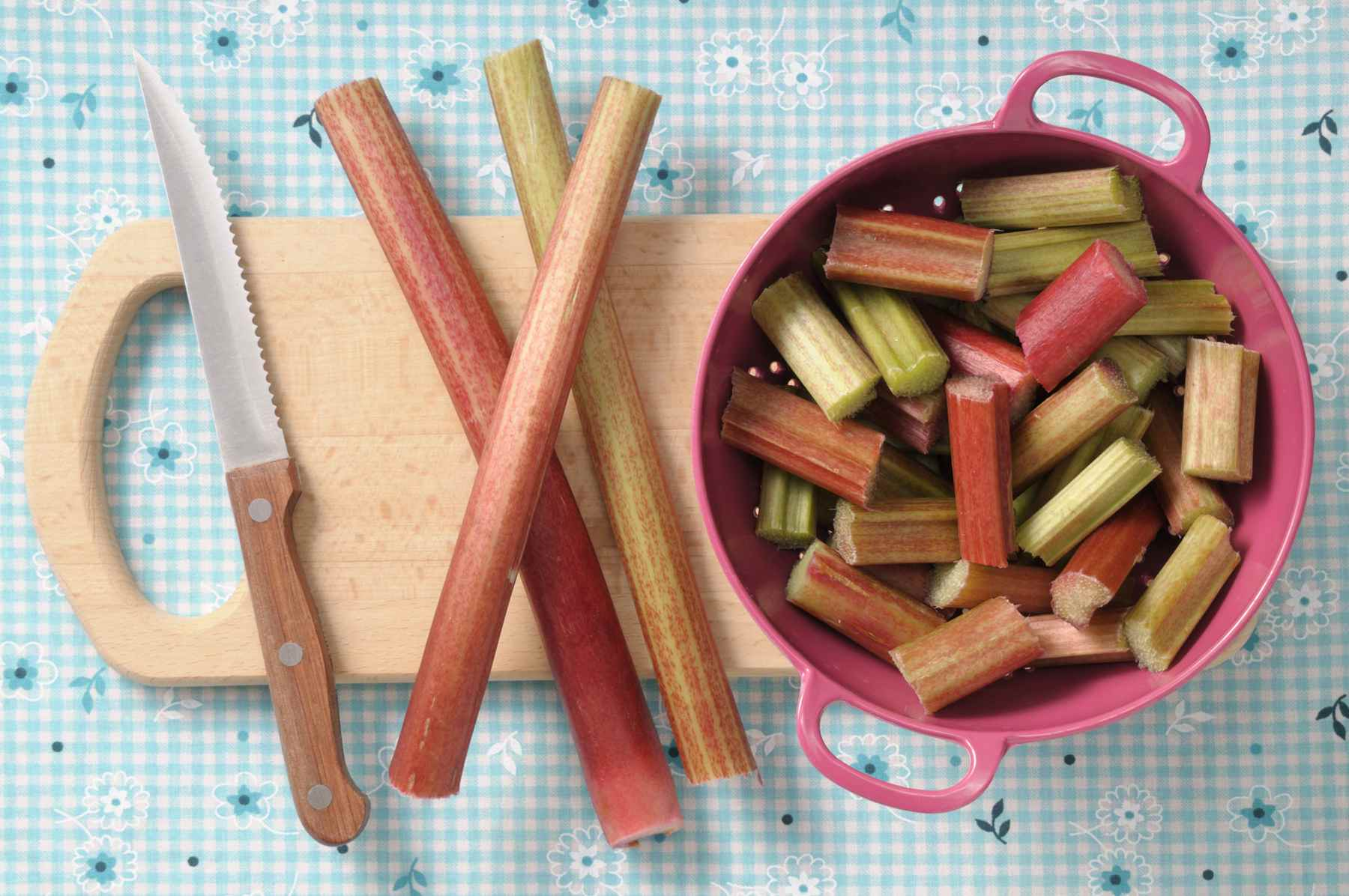 Sliced rhubarb on a cutting board and in a bowl