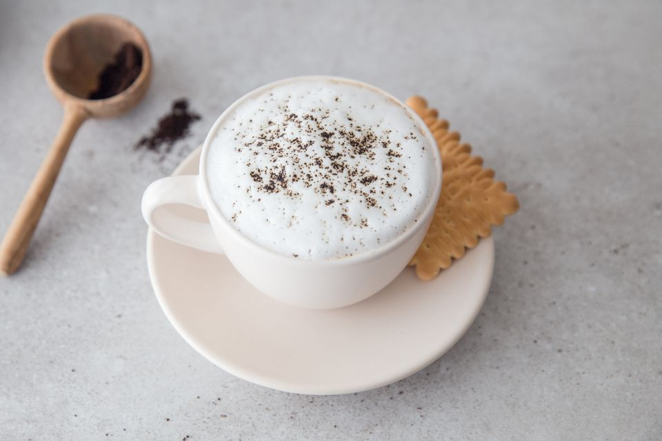 Cafe Latte in a coffee cup with a cookie