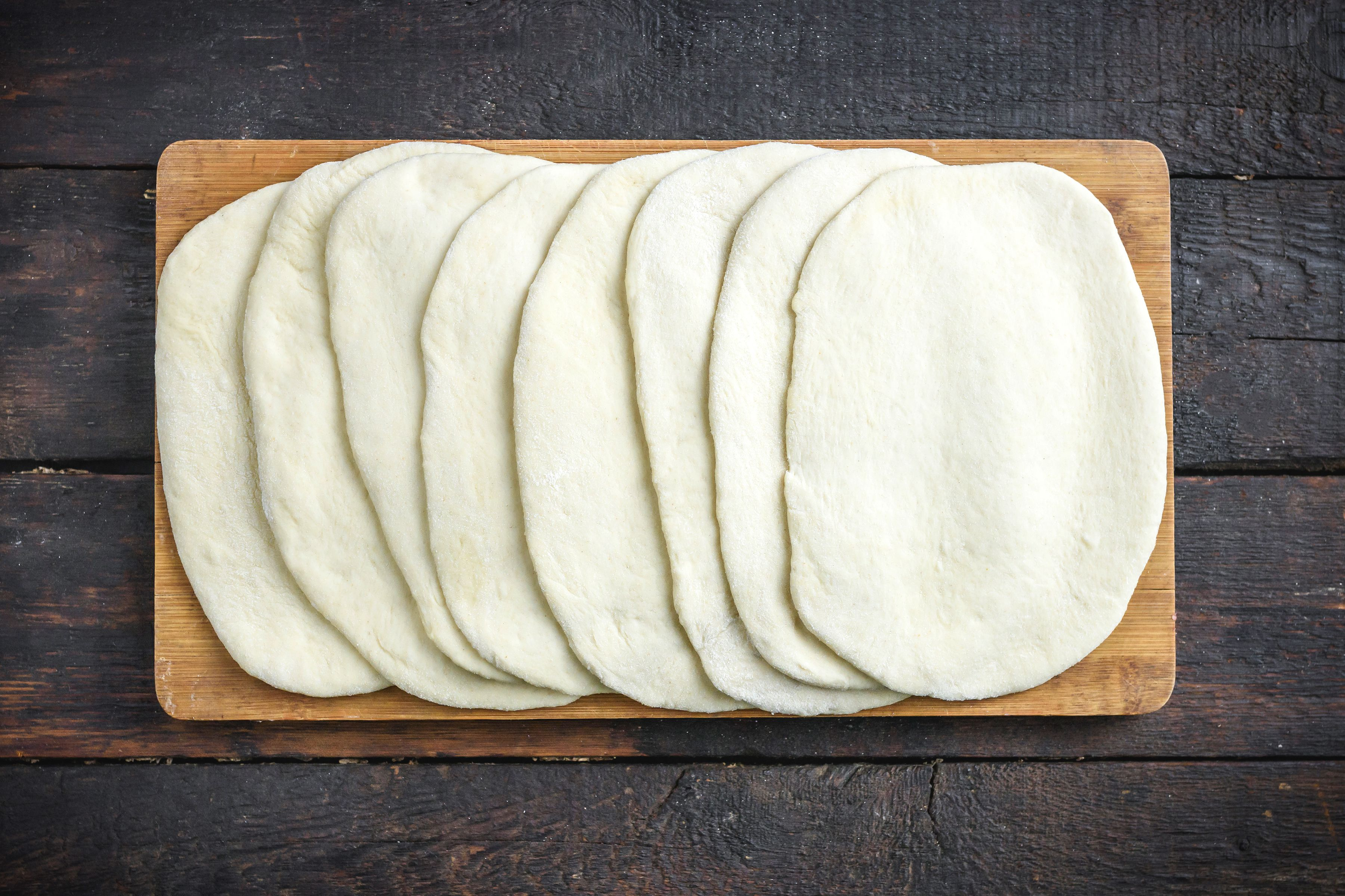 Flatbreads rolled out and stacked on a cutting board