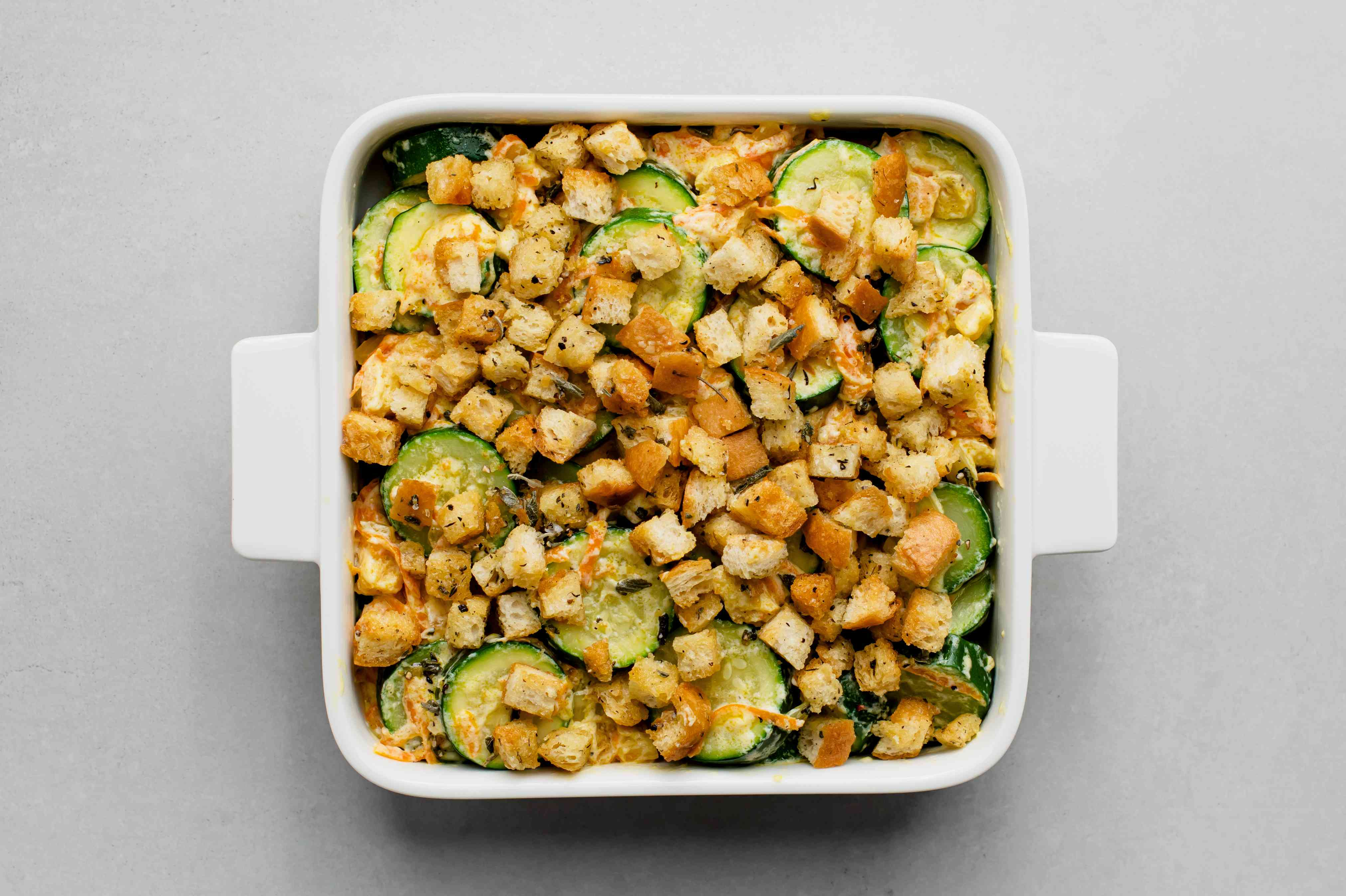 stuffing cubes on top of the zucchini and stuffing mixture